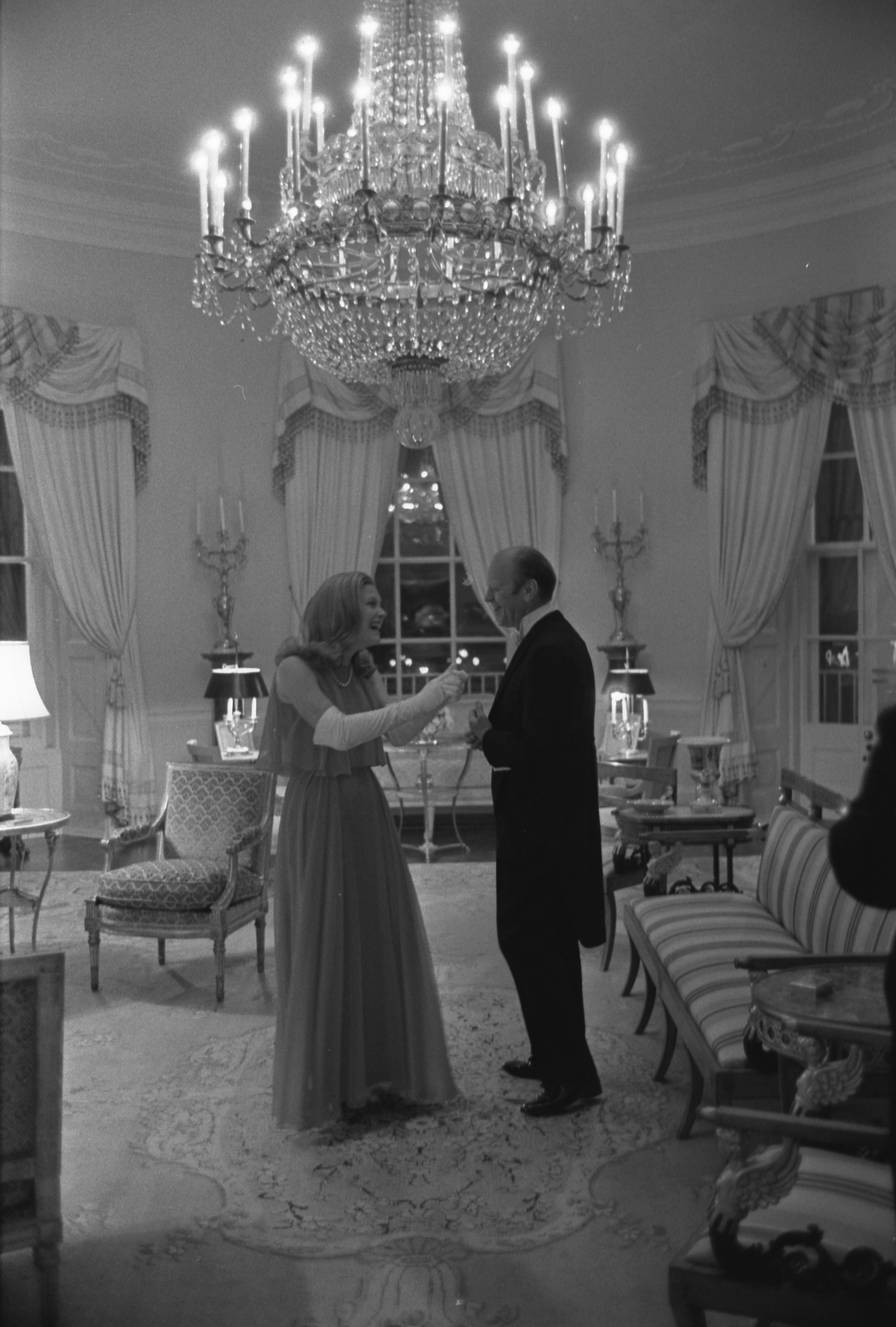 Photograph of Susan Ford Adjusting President Gerald R. Ford's Tuxedo in the Yellow Oval Room prior to a White House Reception for Diplomats