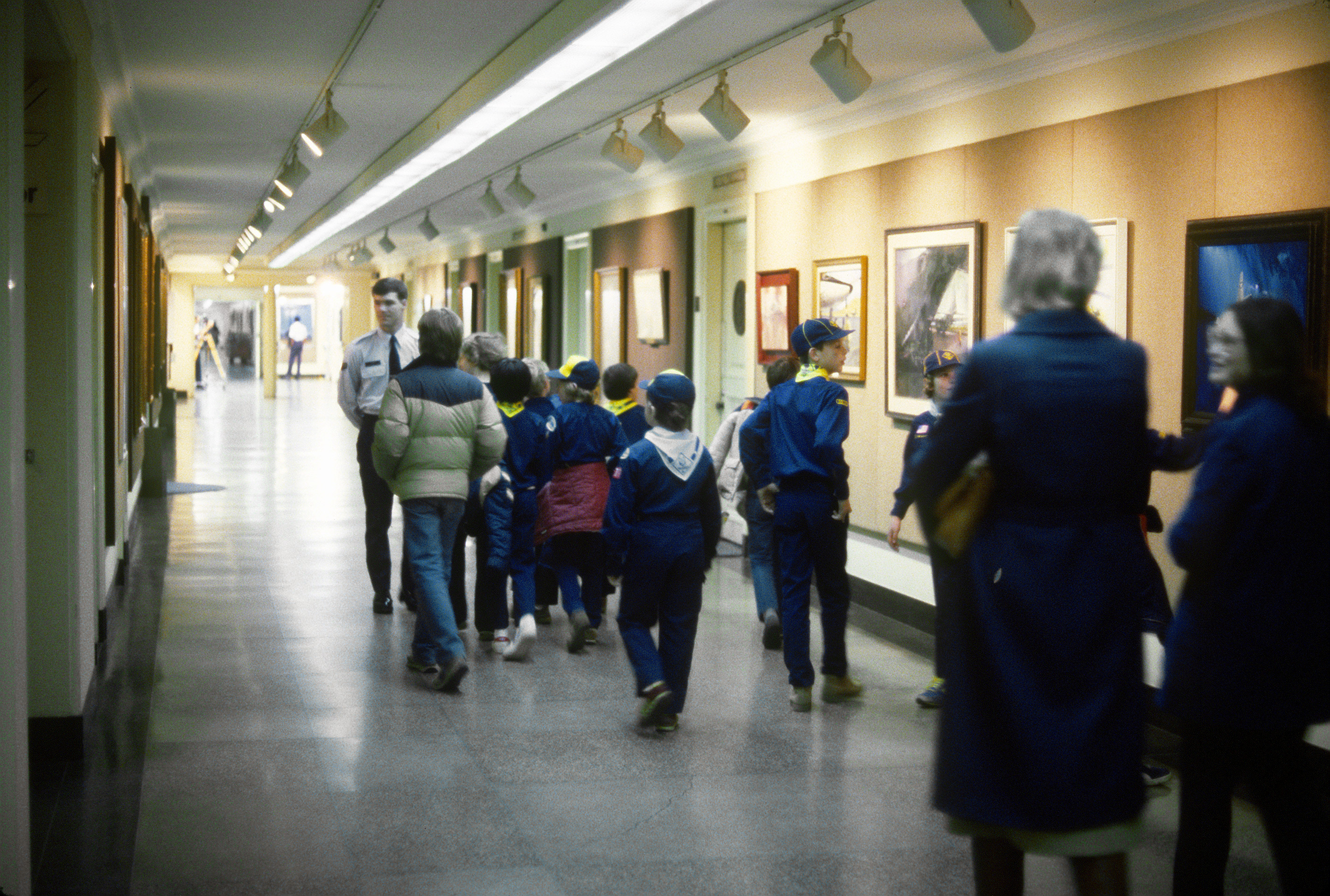 A U.S. Air Force guide explains a painting to Cub Scouts visiting Air Force art exhibitions in the Pentagon