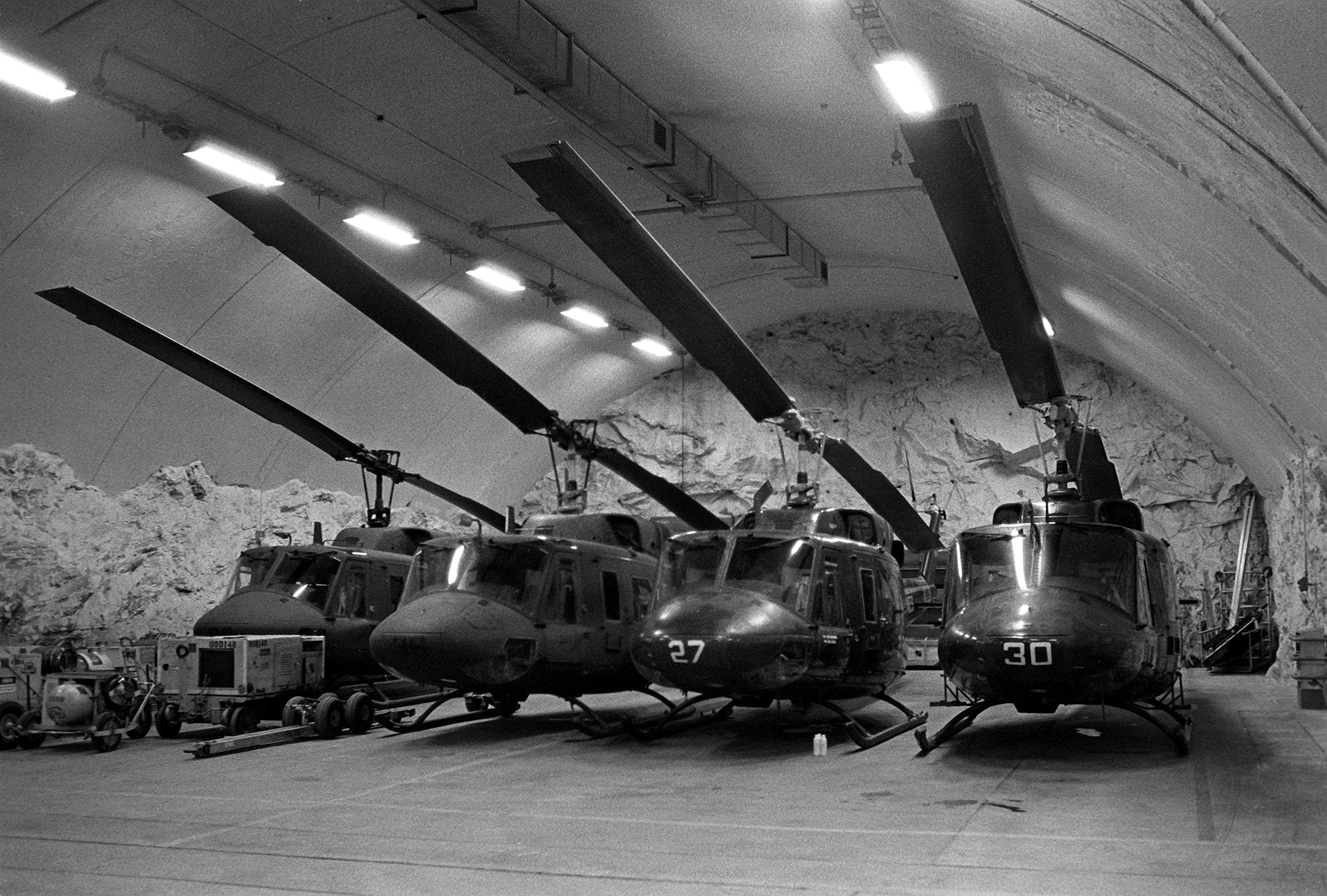 Marine UH-1N Iroquois helicopters are parked in a rock hangar. This area was once used by the Norwegians for aircraft washdowns, repairs and concealment