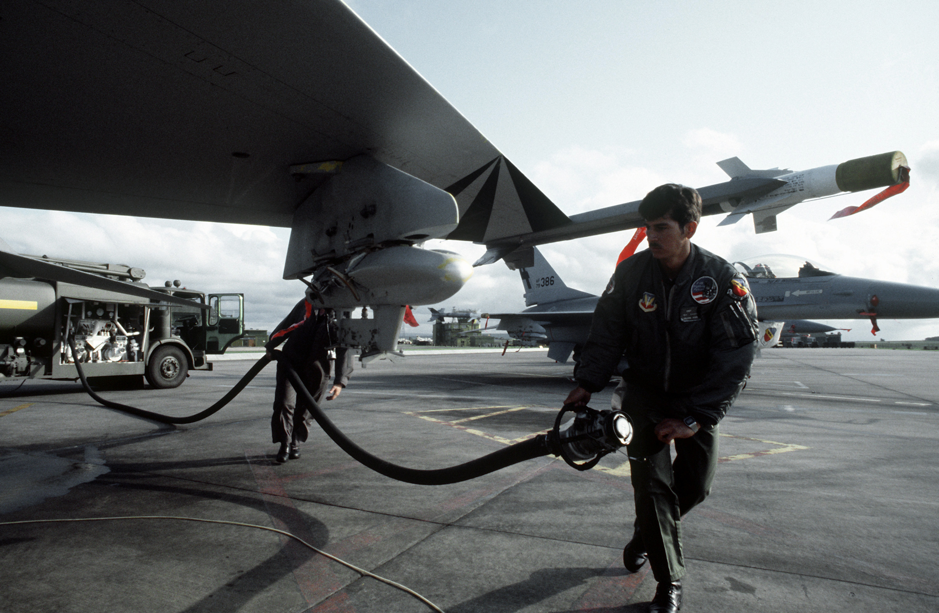 388th Tactical Fighter Wing members prepare to refuel an F-16A Fighting Falcon aircraft during the quick turn competition. The members are involved in the Strike Command Tactical Bombing Competition between the United States and Royal Air Forces. AN AIM-9 Sidewinder missile is shown loaded on the wing tip