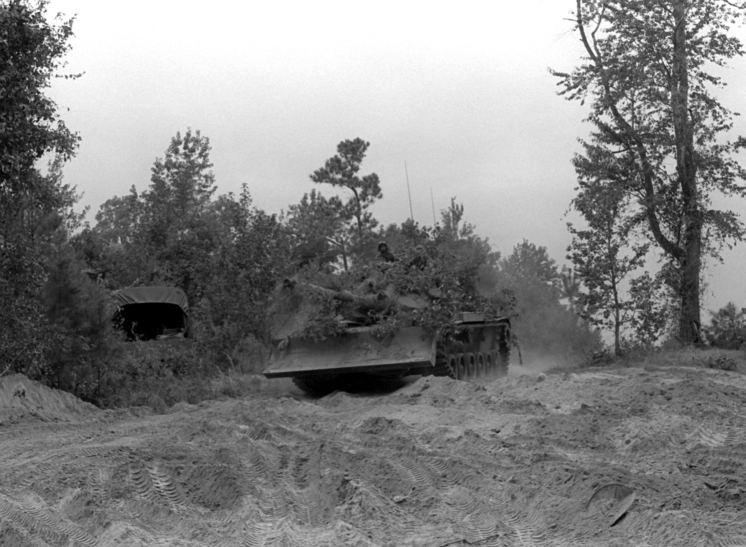 A camouflaged M-60A1 tank from the 8th Marines advances during an exercise