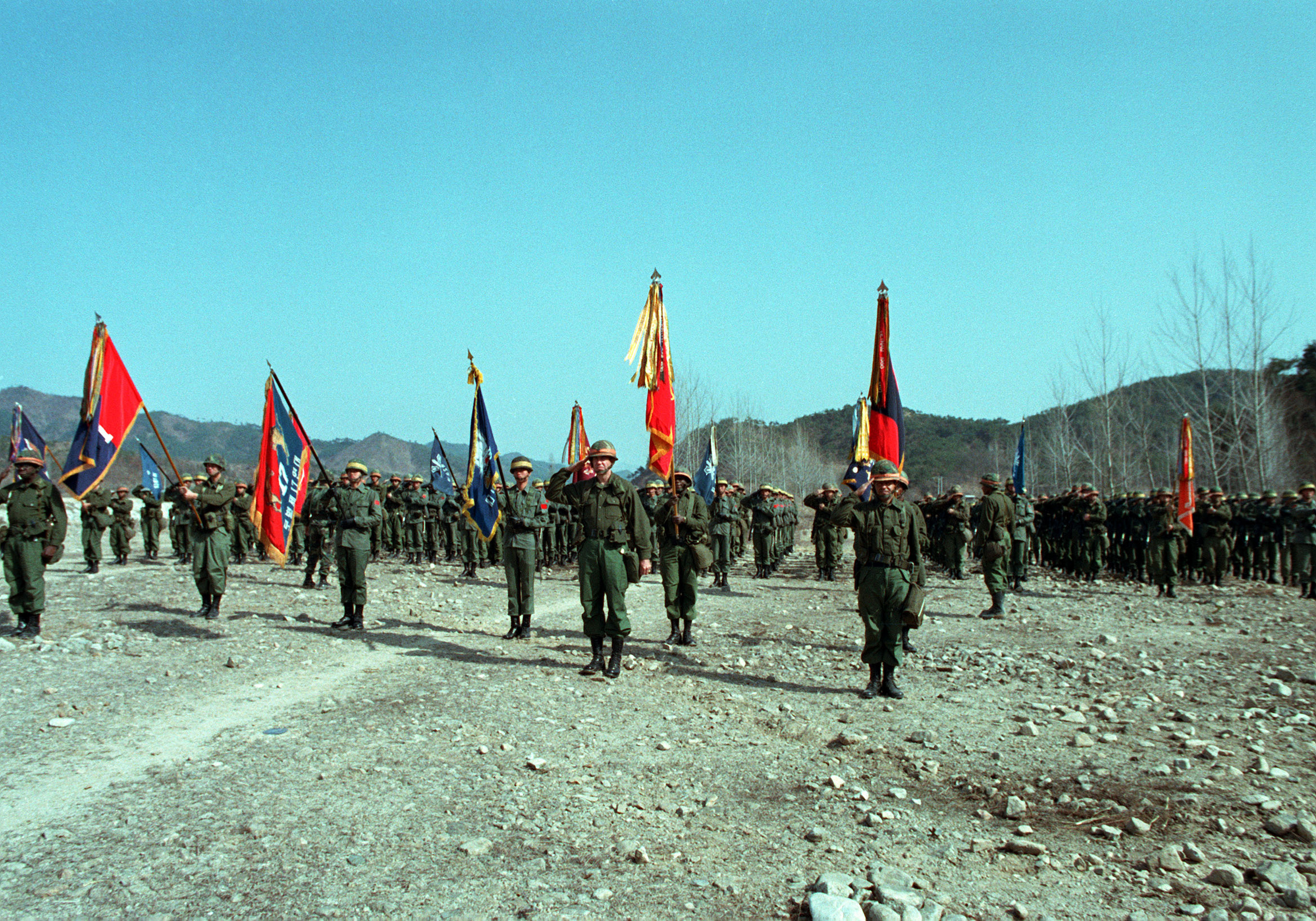 Major General William H. Schneider (center), Commander, 25th Infantry Division, salutes as the Korean and US National Anthems are played during the operational Control ceremony for the joint ROK/US training Exercise TEAM SPIRIT '83