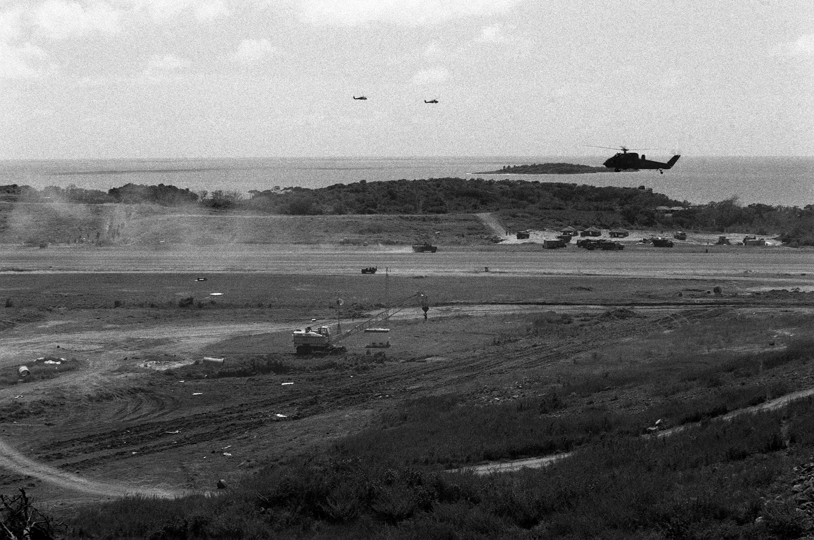Helicopters fly over the Point Salines Airfield runway during the multiservice, multinational Operation URGENT FURY