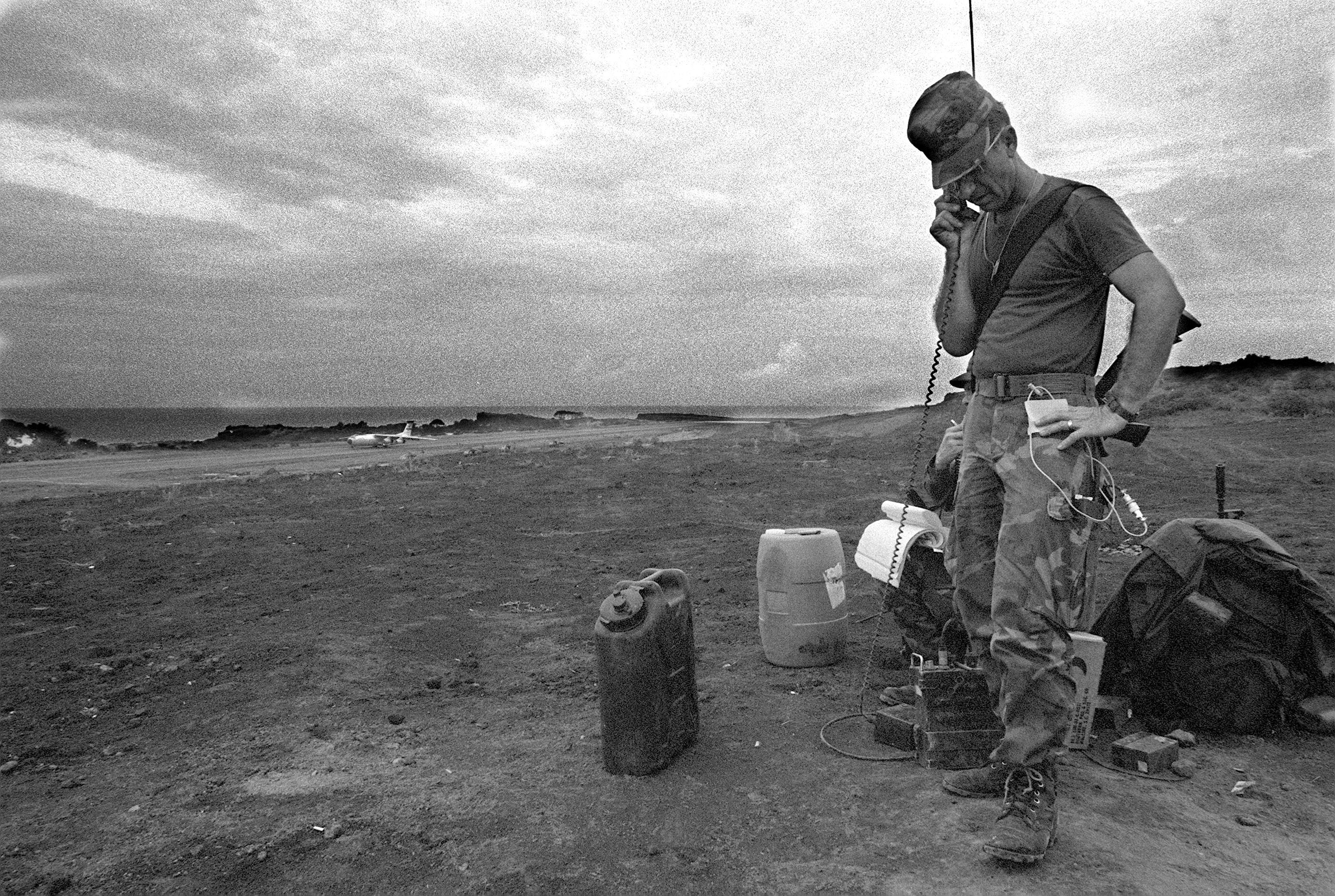 A US serviceman talks on a portable radio near the Point Salines Airfield during the multiservice, multinational Operation URGENT FURY