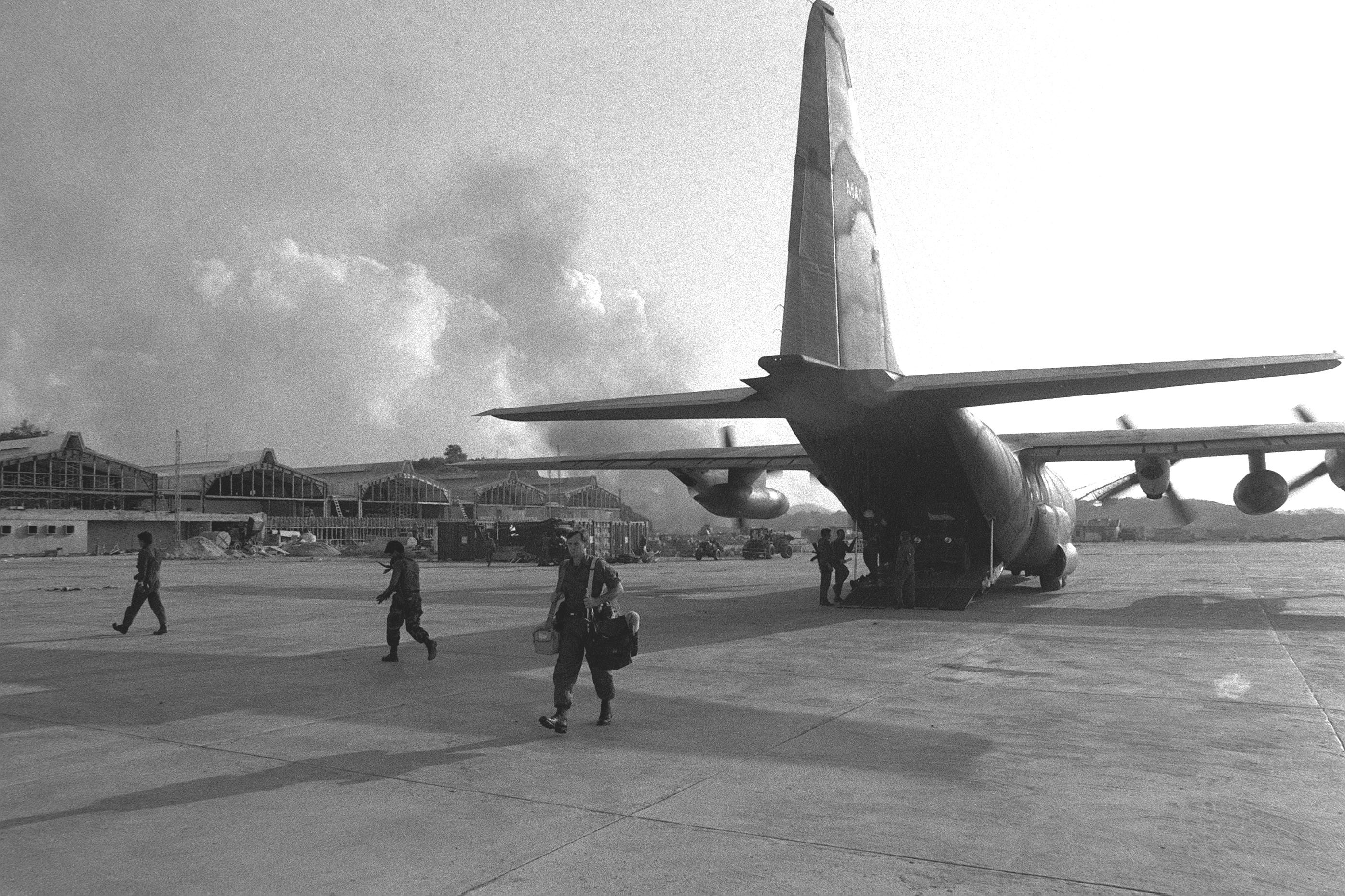 Equipment is offloaded from a C-130 Hercules aircraft at Point Salines Airfield during the multiservice, multinational Operation URGENT FURY