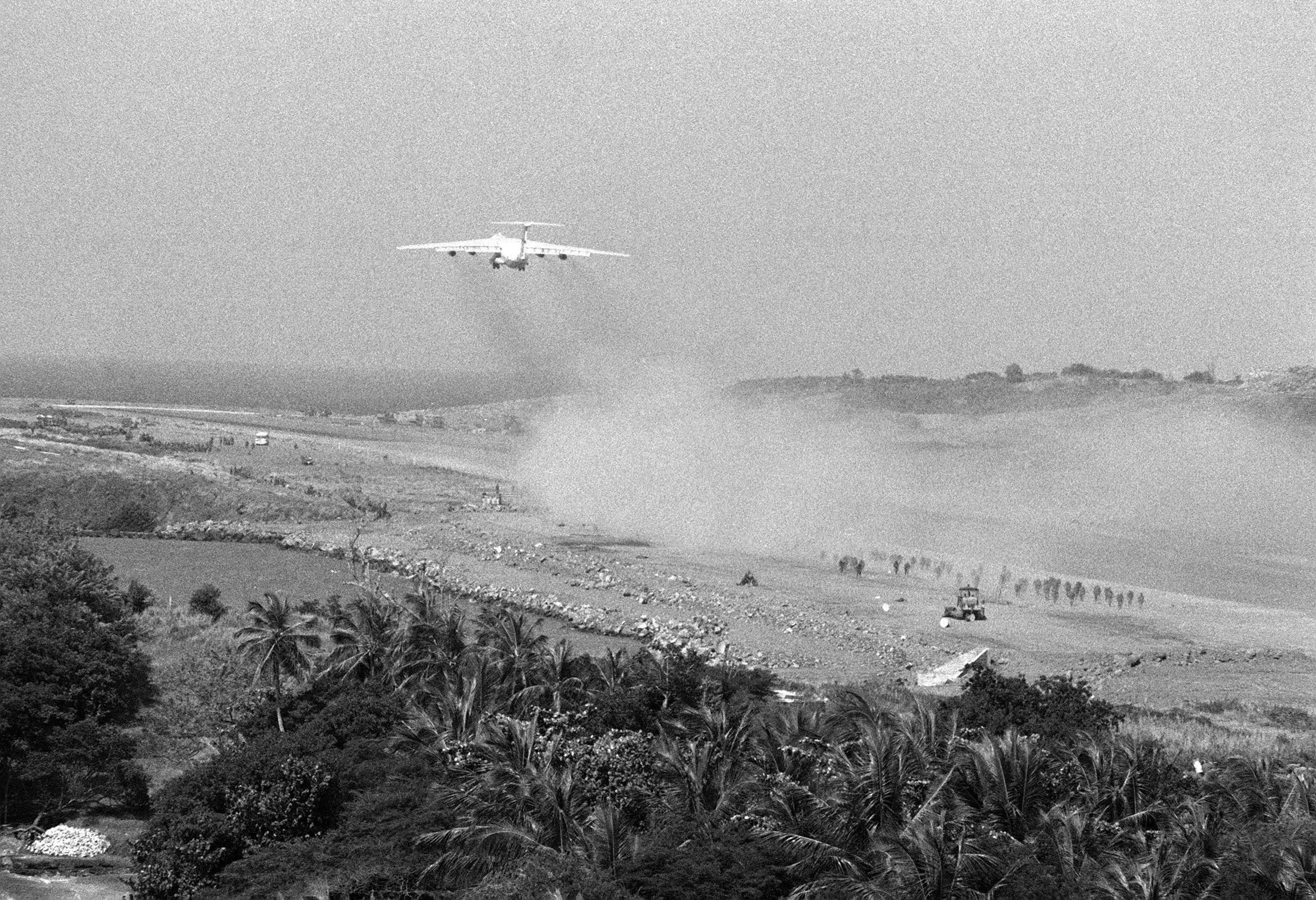 A C-141B Starlifter aircraft takes off from Point Salines Airfield runway during the multiservice, multinational Operation URGENT FURY