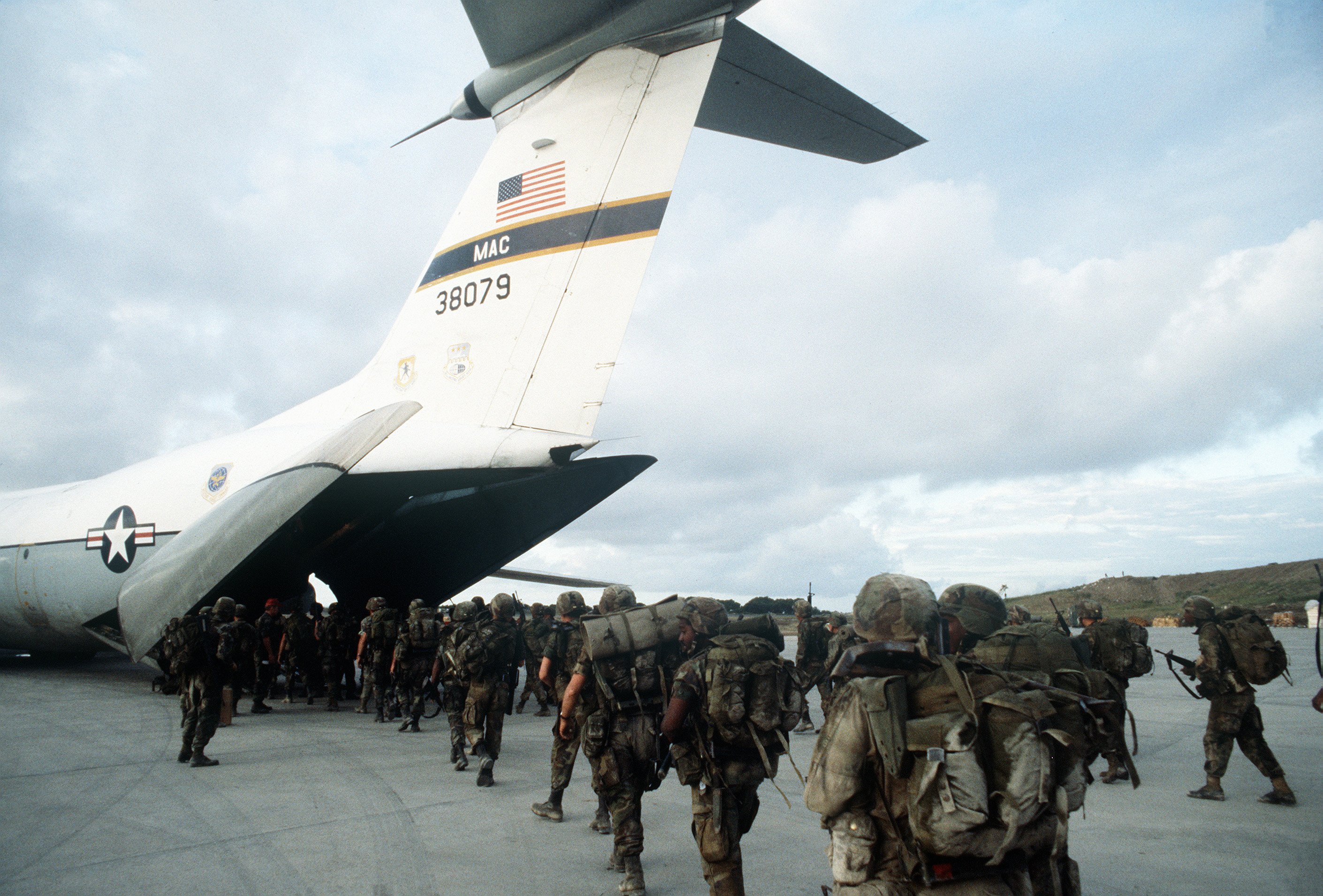 US military personnel board a C-141B Starlifter aircraft at Point Salines Airport during Operation URGENT FURY
