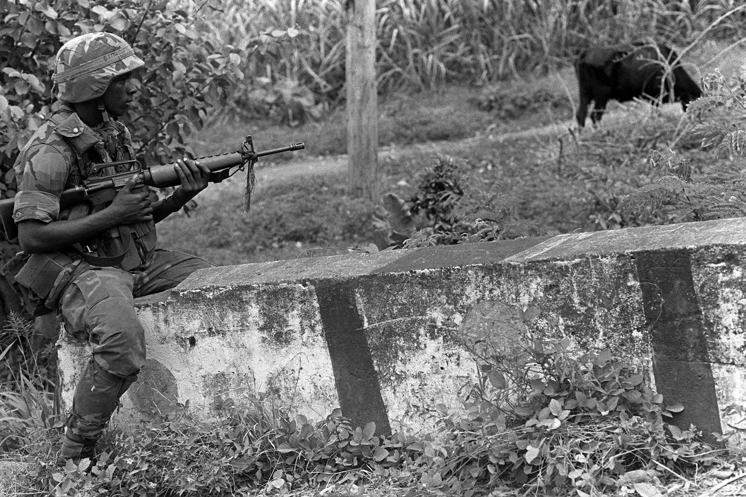 A soldier, armed with an M16A1 rifle, patrols the area around Point Salines Airport Operation URGENT FURY