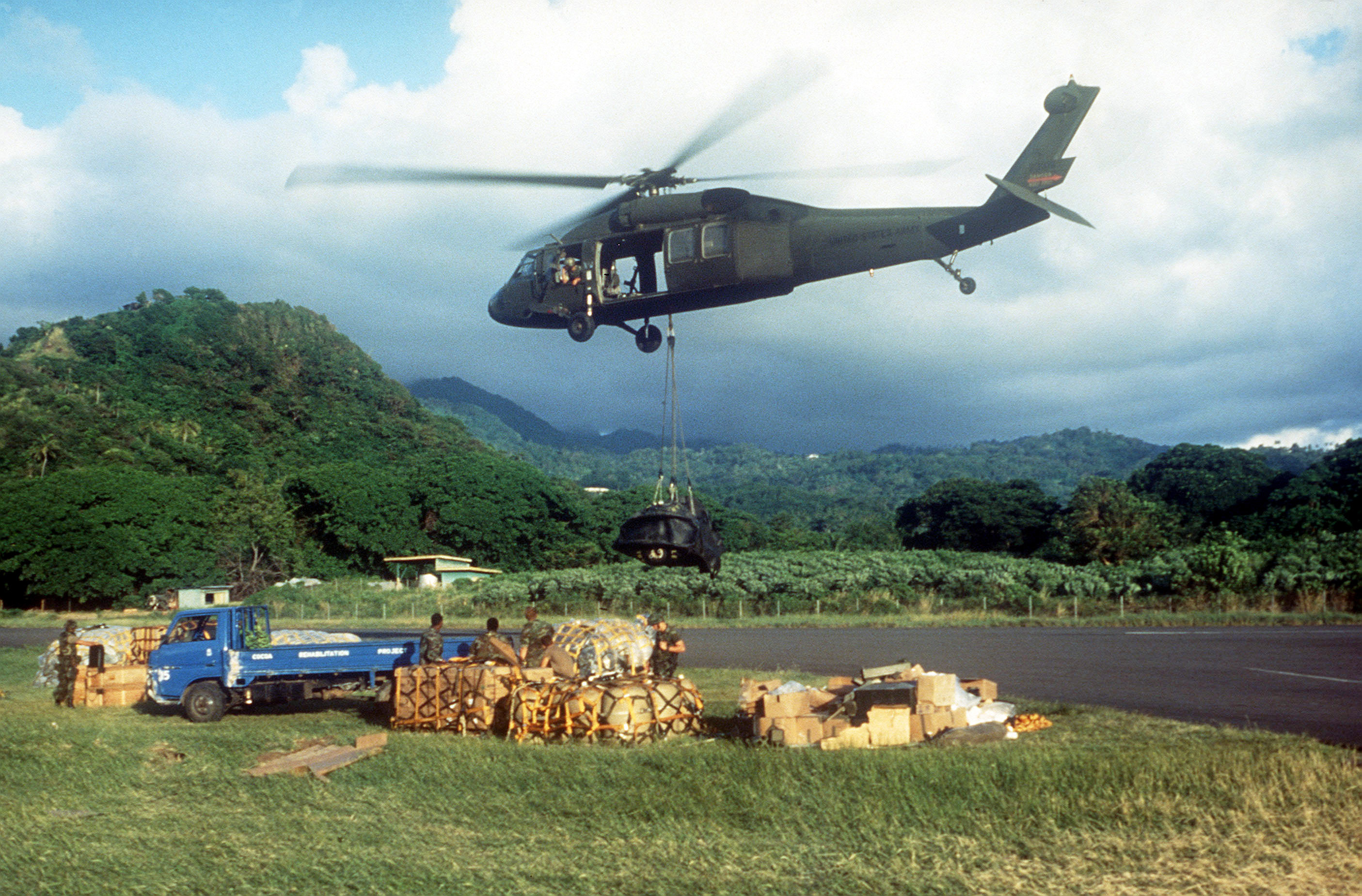 A UH-60 Black Hawk (Blackhawk) helicopters lowers a pallet of supplies at Point Salines Airport during Operation URGENT FURY