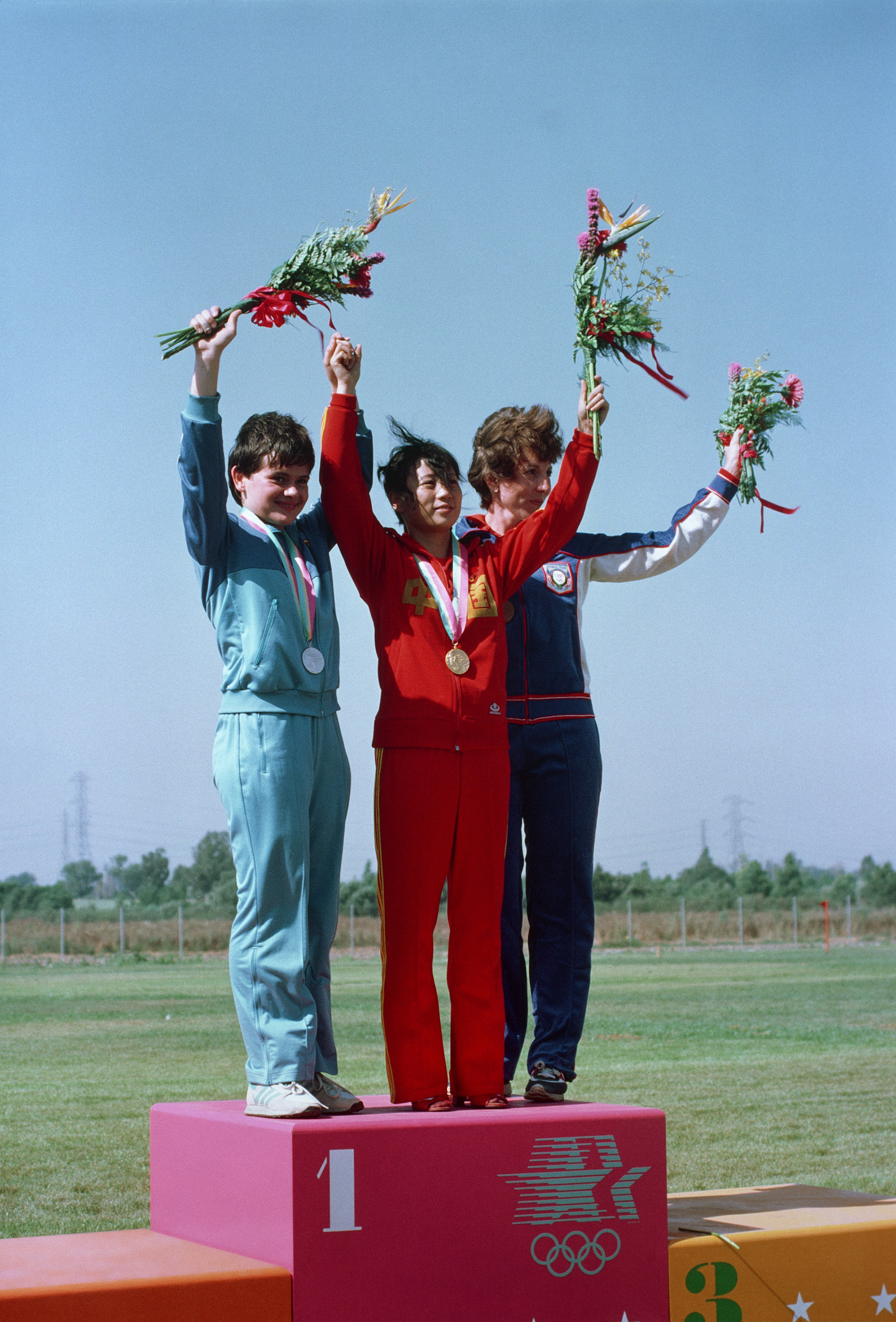 Army Reserve Captain Wanda R. Jewell, right, stands with the gold and silver medalist after receiving a bronze medal in the small-bore rifle English competition at the 1984 Summer Olympics