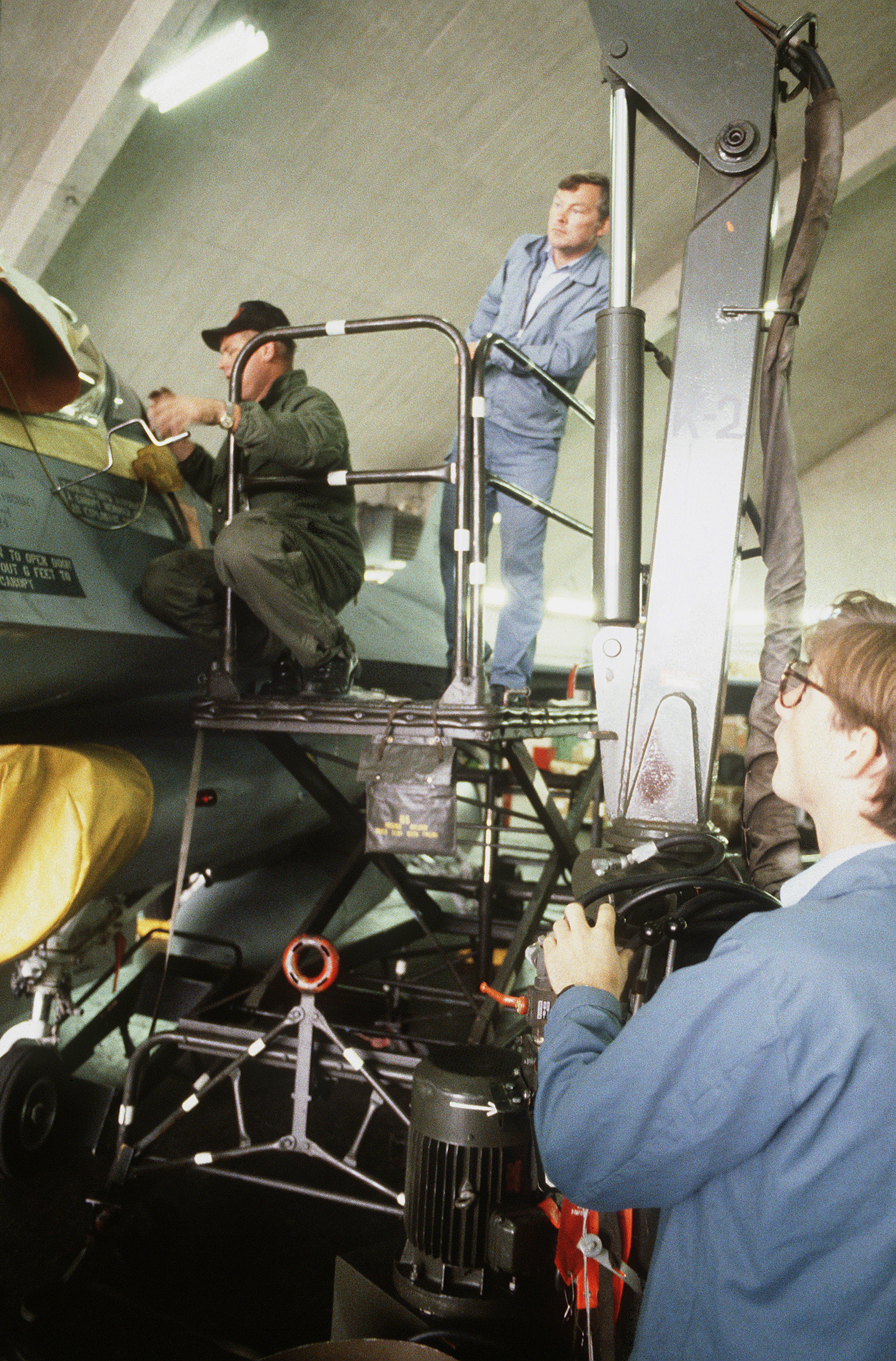 Norwegians work with members of the 19th Tactical Fighter Squadron, as they prepare to change the canopy on an F-16 Fighting Falcon aircraft with a winch during Exercise CORNET GAUNTLET '83