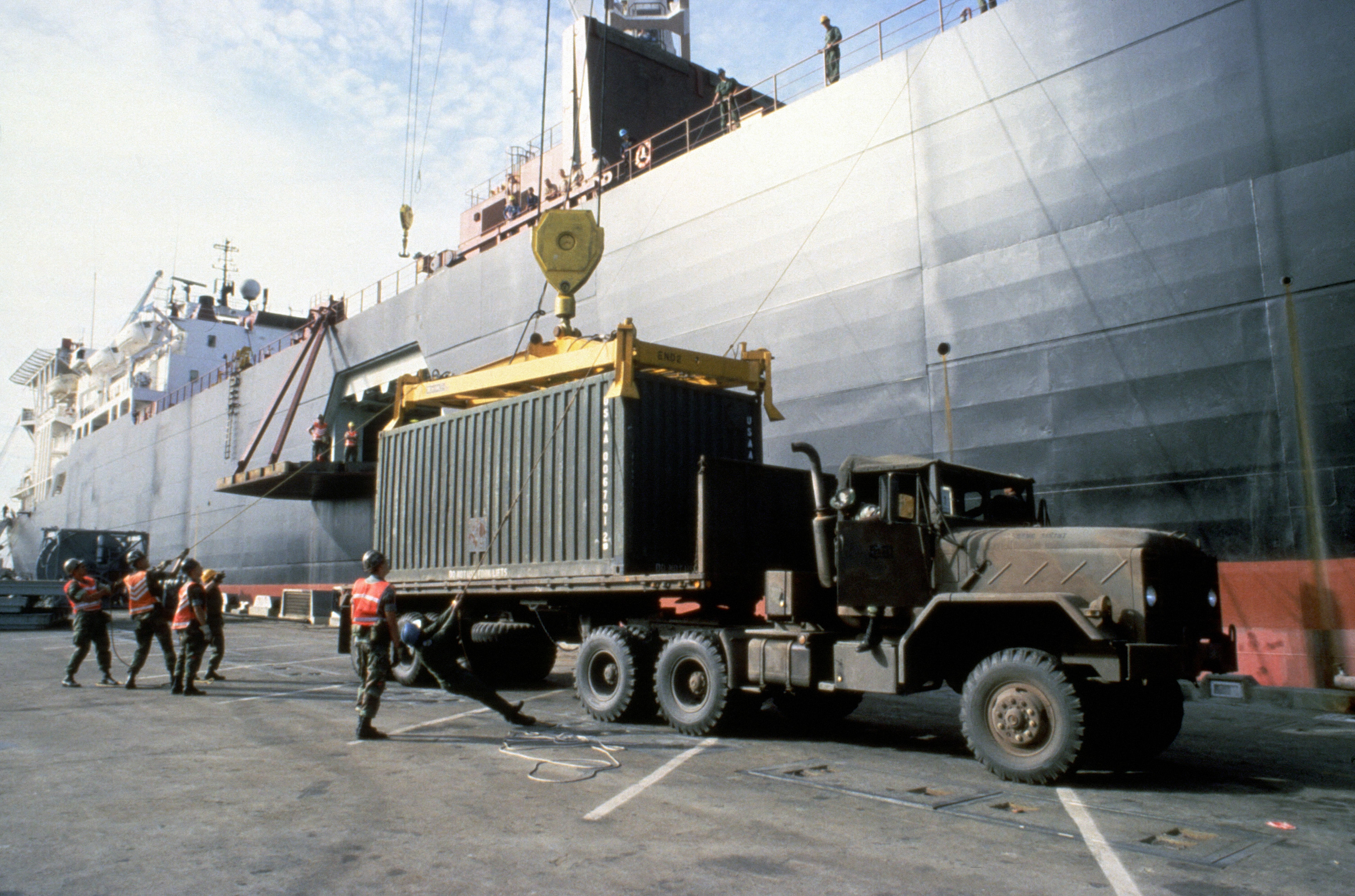 Containerized cargo of the 6th Marine Amphibious Brigade is loaded aboard the Maersk class maritime prepositioning ship SS CPL. LOUIS J. HAUGE JR. The container is being lifted from a trailer towed by an M931 5-ton tractor