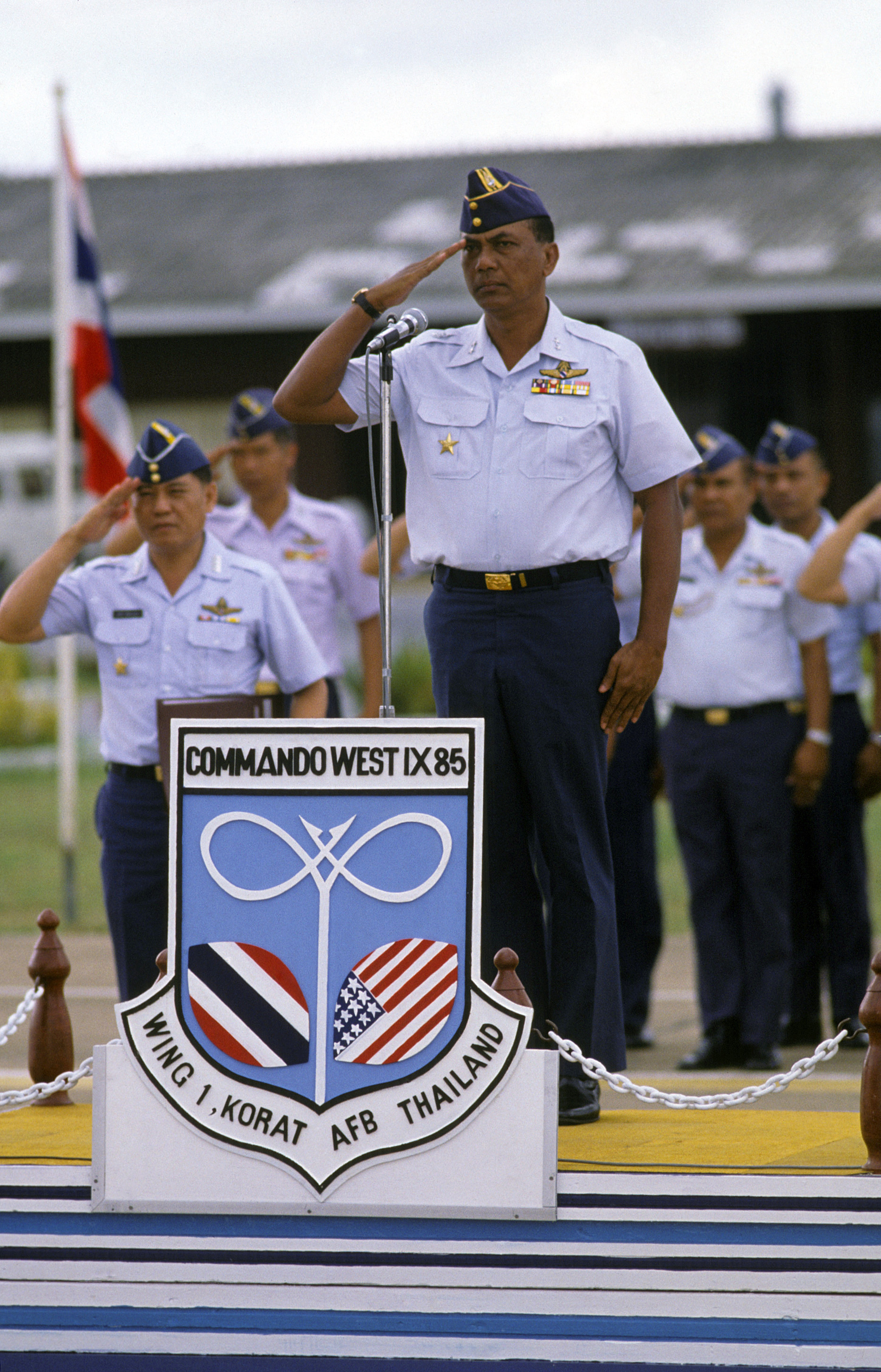 Air Marshall Gunn, Royal Thai Air Force, salutes as the national anthems of Thailand and the United States are played. The two countries are participating in COMMANDO WEST IX, a joint US and Thailand training exercise