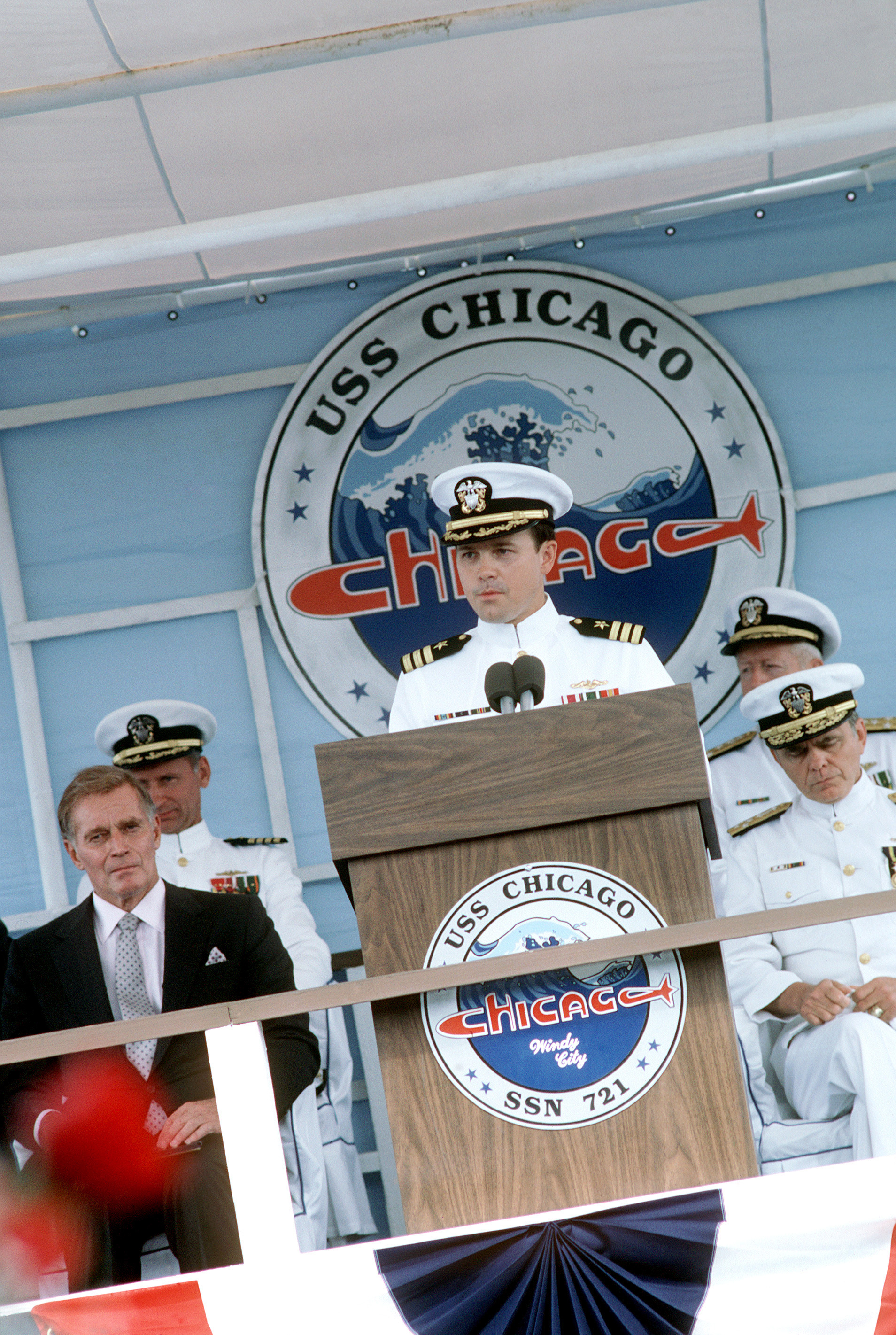 Commander (CDR) Robert B. Avery, commanding officer of the nuclear-powered attack submarine USS CHICAGO (SSN 721) speaks during the ship's commissioning. Actor Charlton Heston is seated to the left and Admiral (ADM) Kinnard R. McKee, director, Naval Nuclear Propulsion Program, is at the right