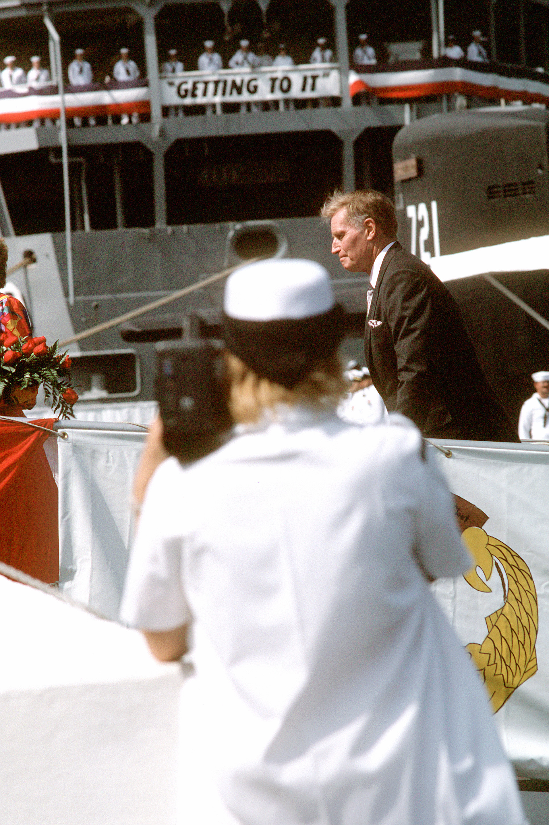 Actor Charlton Heston crosses the brow of the nuclear-powered attack submarine USS CHICAGO (SSN 721) after delivering the principal address during the ship's commissioning