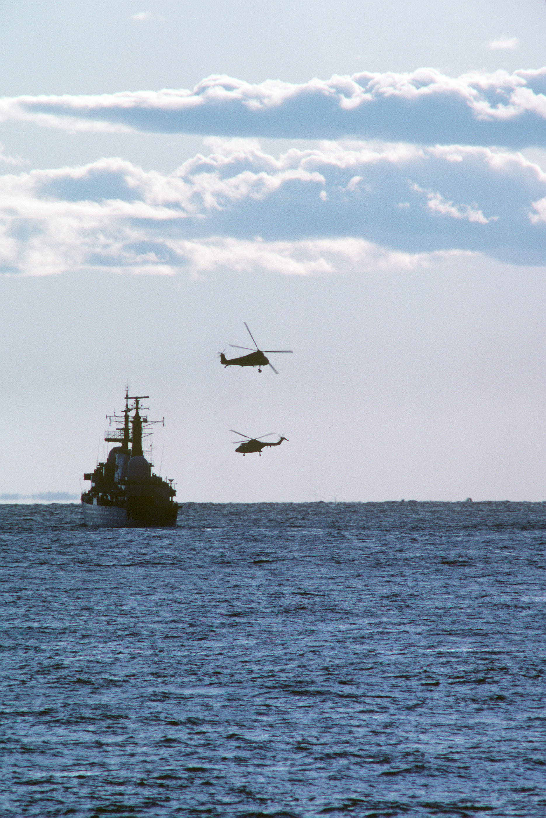 A silhouetted view of a NATO warship with two anti-submarine warfare helicopters flying nearby during NATO Exercise NORTHERN WEDDING 86
