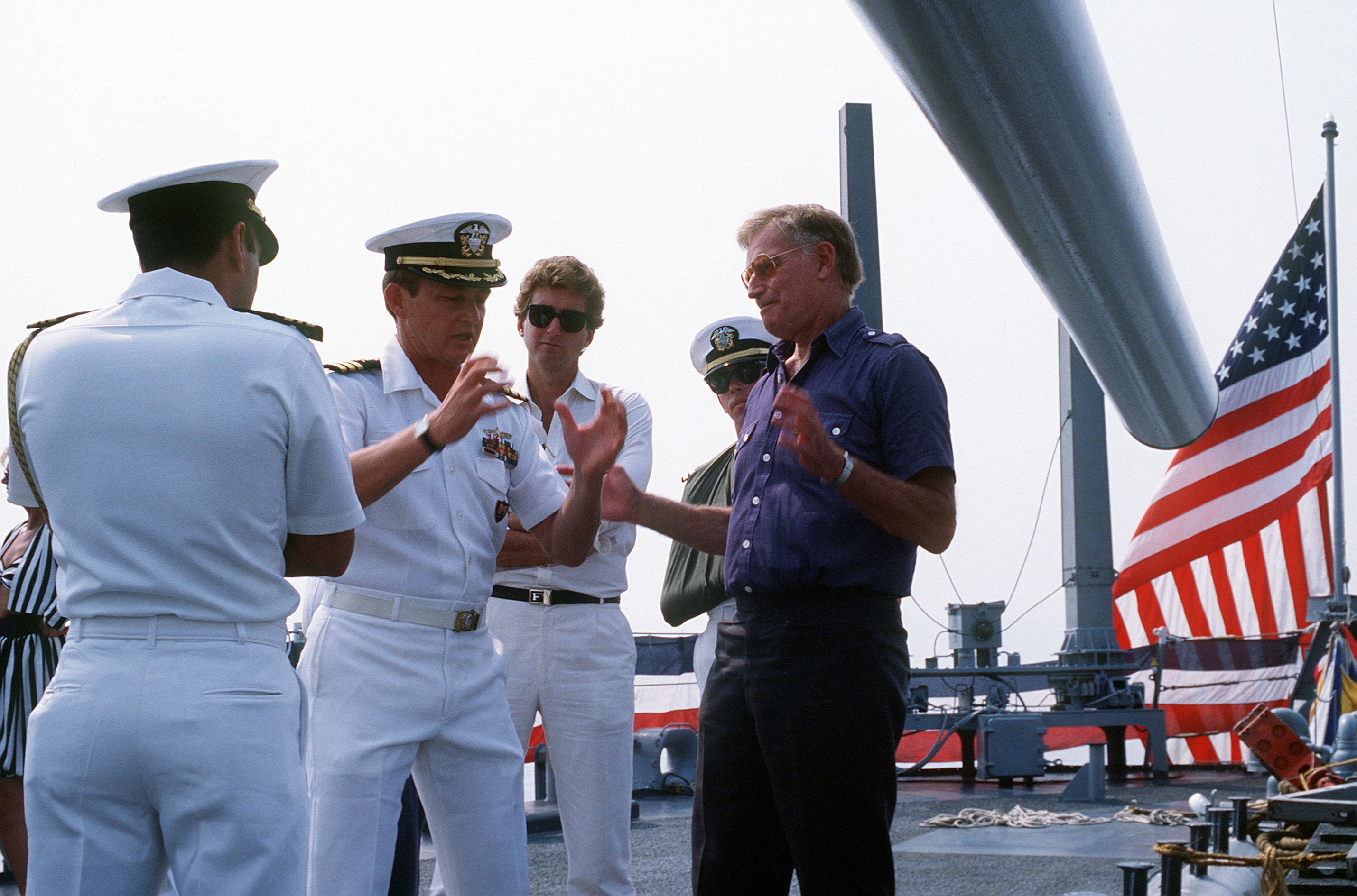 An officer explains ship operations to actor Charlton Heston on the deck of the guided missile cruiser USS BELKNAP (CG-26). The BELKNAP and other U.S. Navy vessels are visiting Cannes during the July 4th celebration sponsored by the United Services Organization (USO) at the Cannes Film Festival Hall. Festival events include a parade of World War II vehicles, a concert for residents and visitors and a gala dinner-dance for special guests