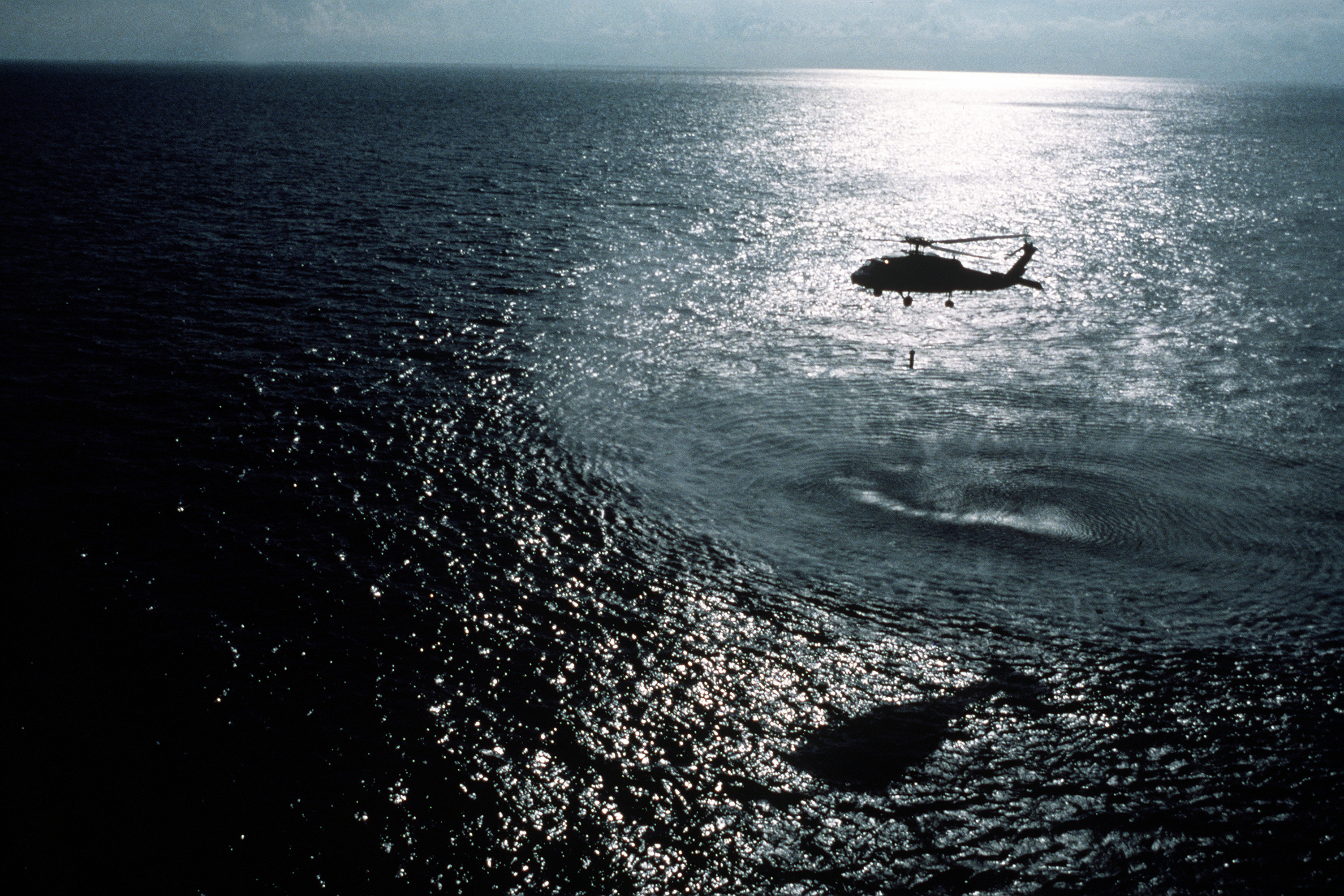 An SH-60F Seahawk helicopter lowers a dipping sonar detector during an anti-submarine warfare support operation