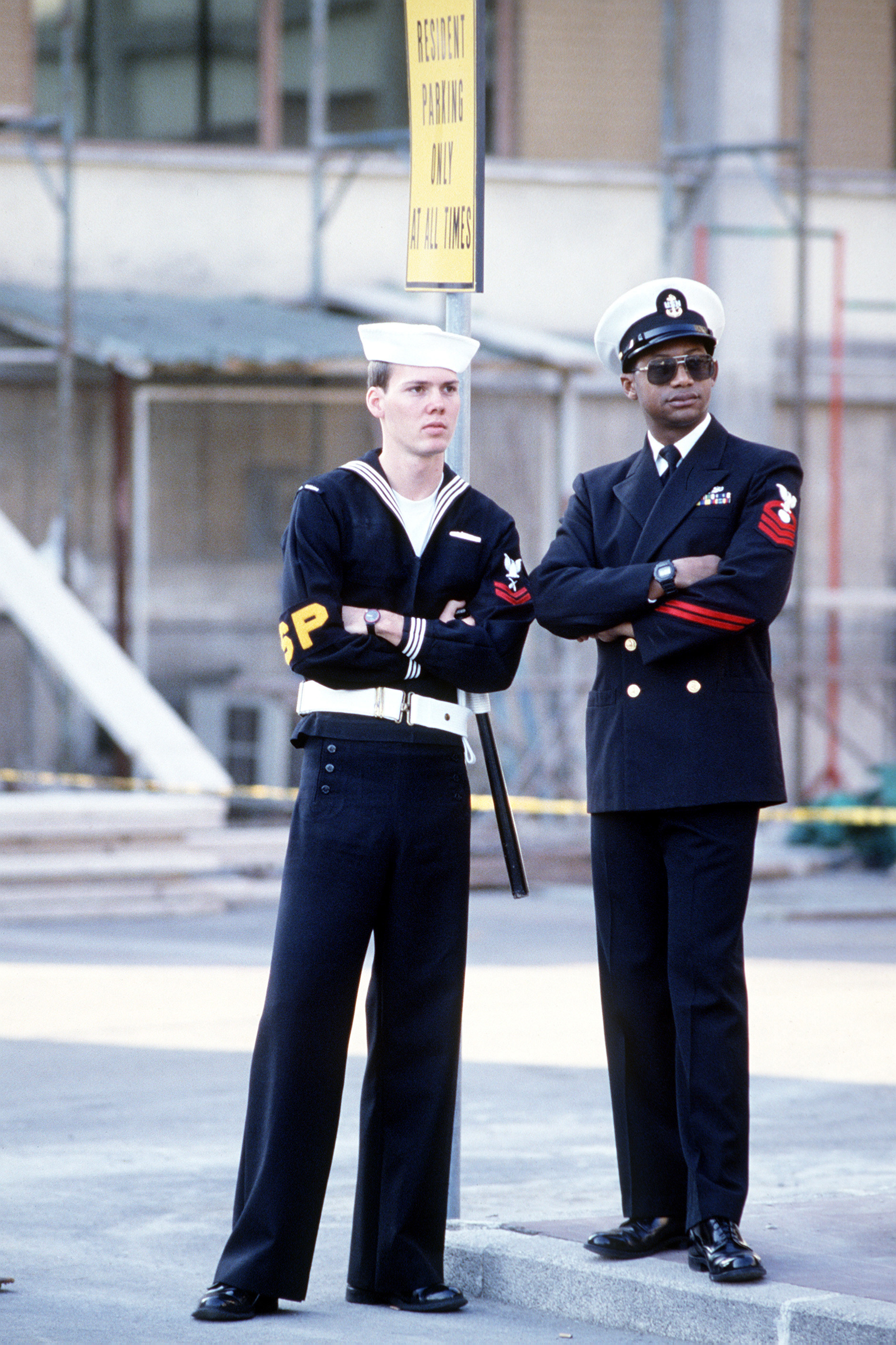 A chief petty officer (CPO) stands beside a sailor on shore patrol duty to watch a performance by the 6th Fleet Band, the