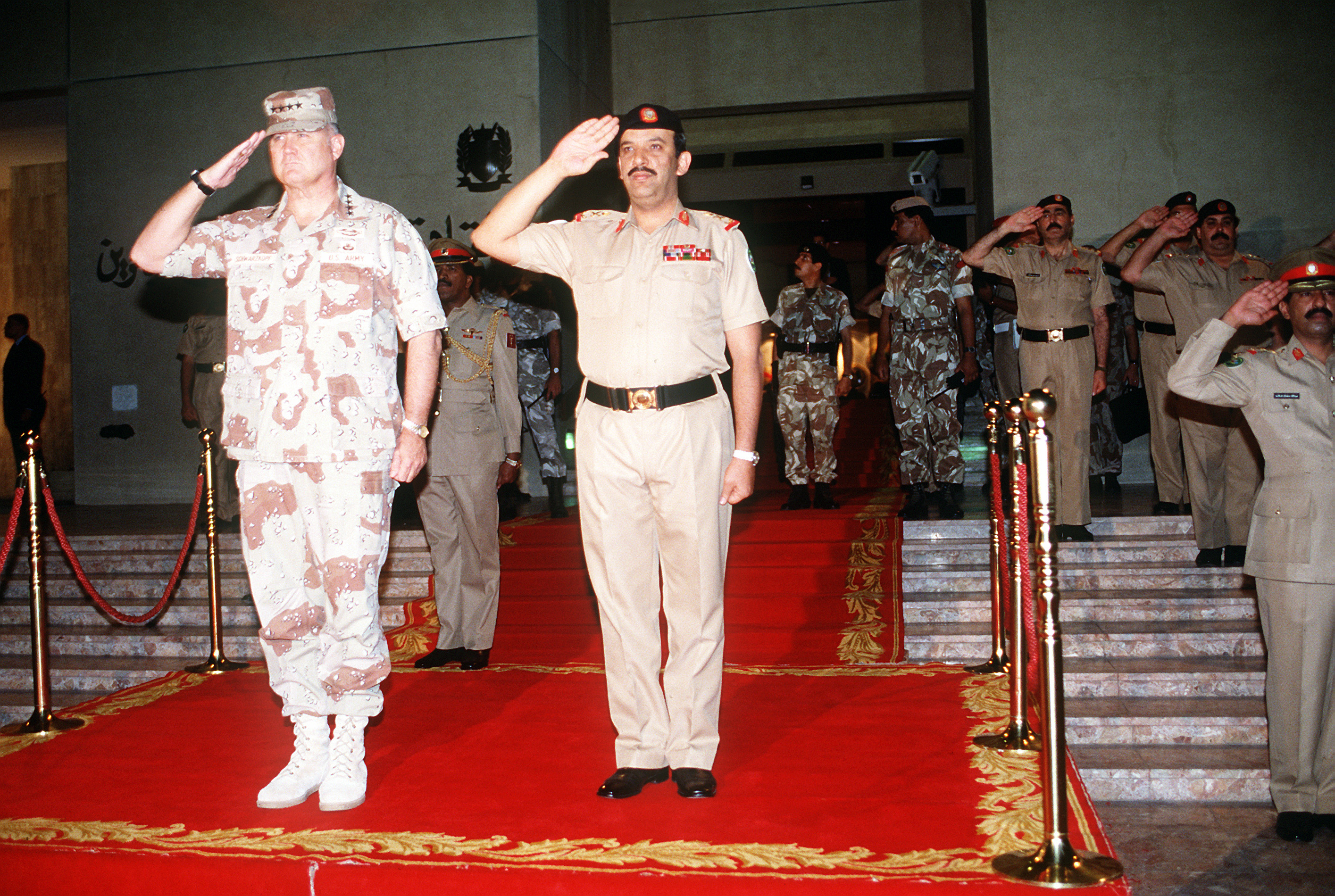 GEN. Norman Schwarzkopf, commander-in-chief, U.S. Central Command, and MAJ. GEN. Shaikh Khalifa Bin Ahmed Al-Khalifa, minister of defense, present arms as the U.S. and Bahraini national anthems are played during a ceremony at the Bahrain defense forces headquarters commemorating the Allied success during Operation Desert Storm.