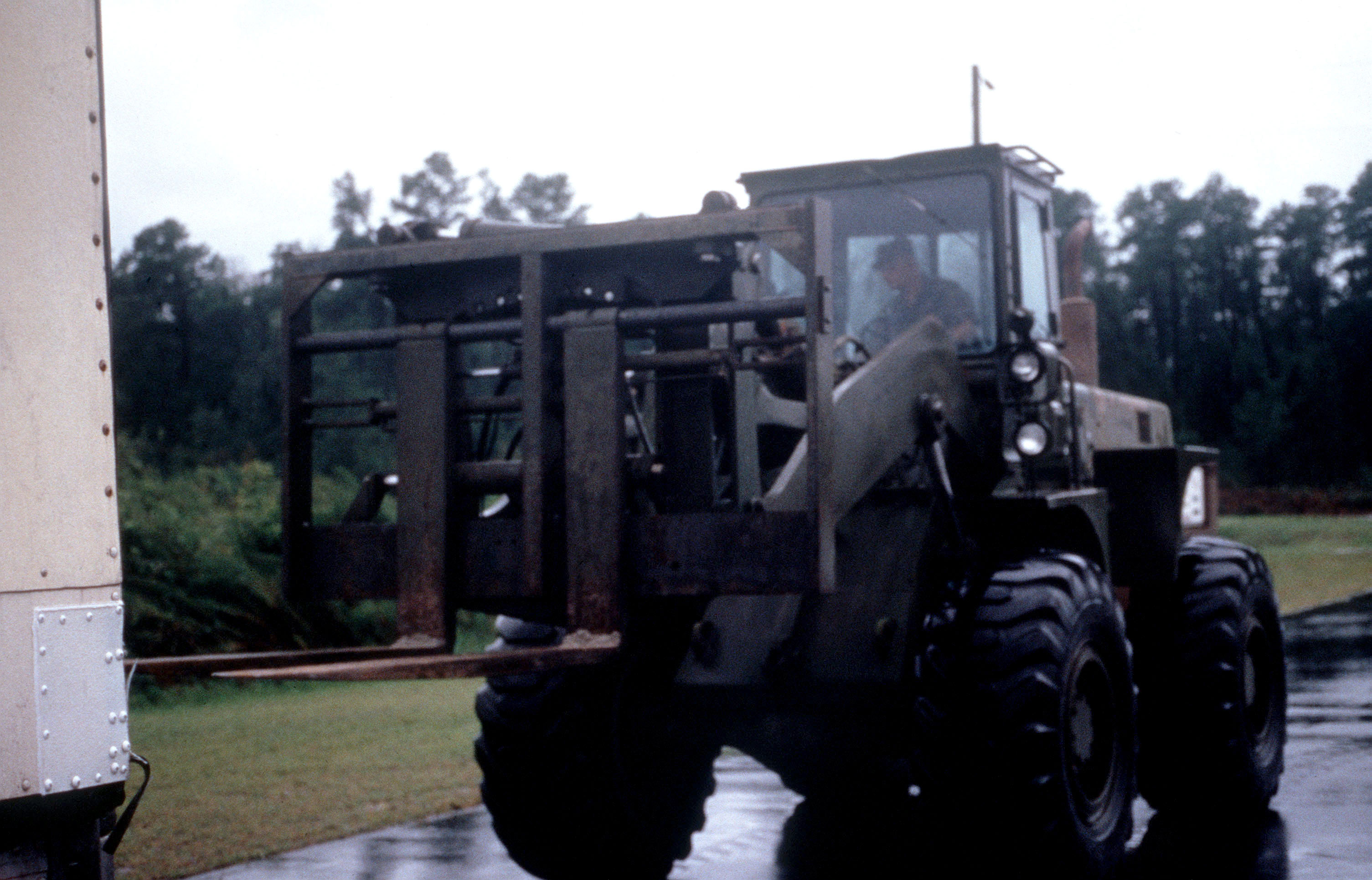 An Army National Guard soldier from Kinston Armory, Kinston, North Carolina drives a heavy forklift truck towards a commercial trailer to off-load pallets of bottled water after Hurricane Bonnie