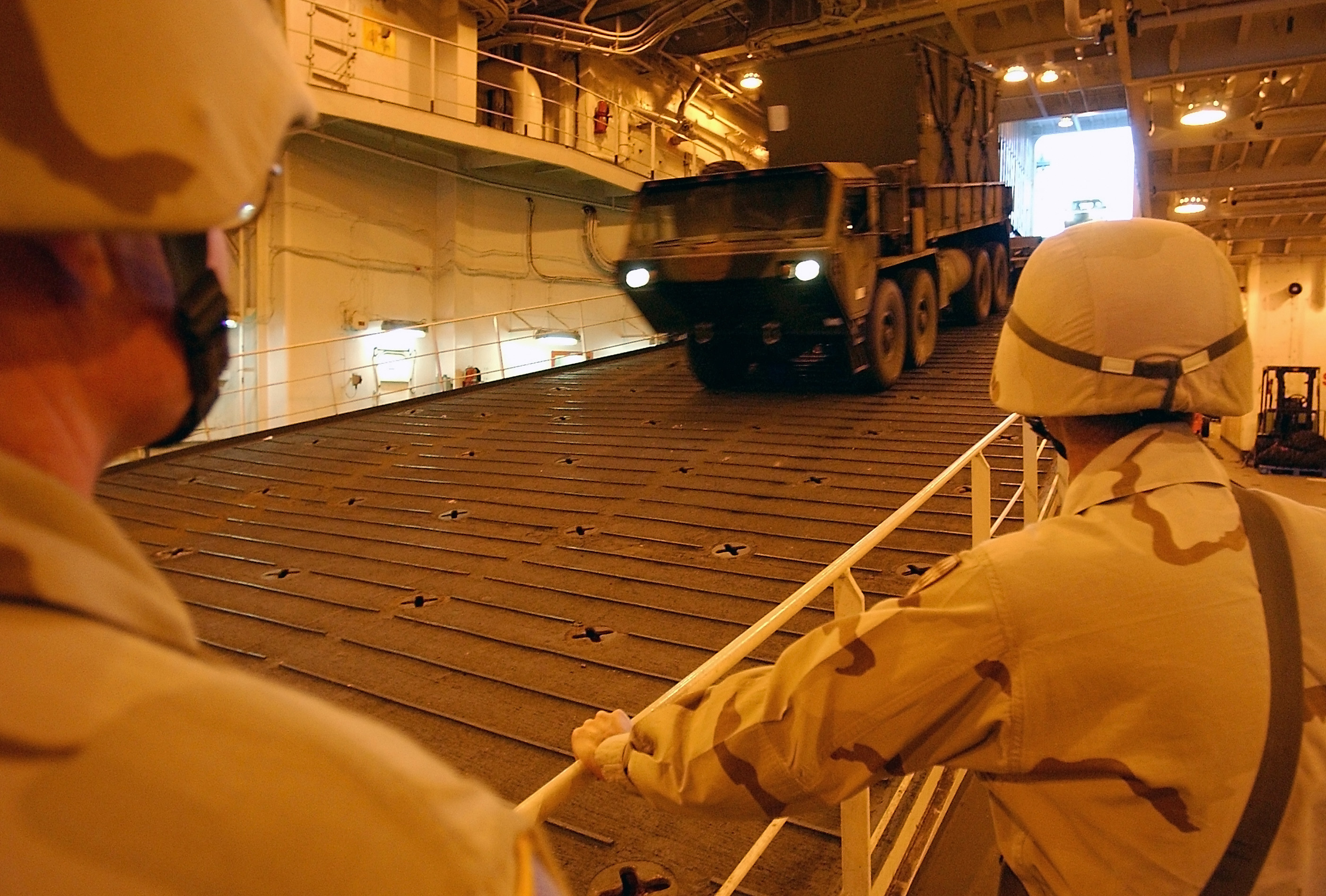 US Army (USA) Soldiers assigned to the 32nd Army Air and Missile Defense Company observe as vehicles a driven down a ramp while offloading from navy cargo vessels at the Port of As Shauybah, Kuwait, during Operation ENDURING FREEDOM