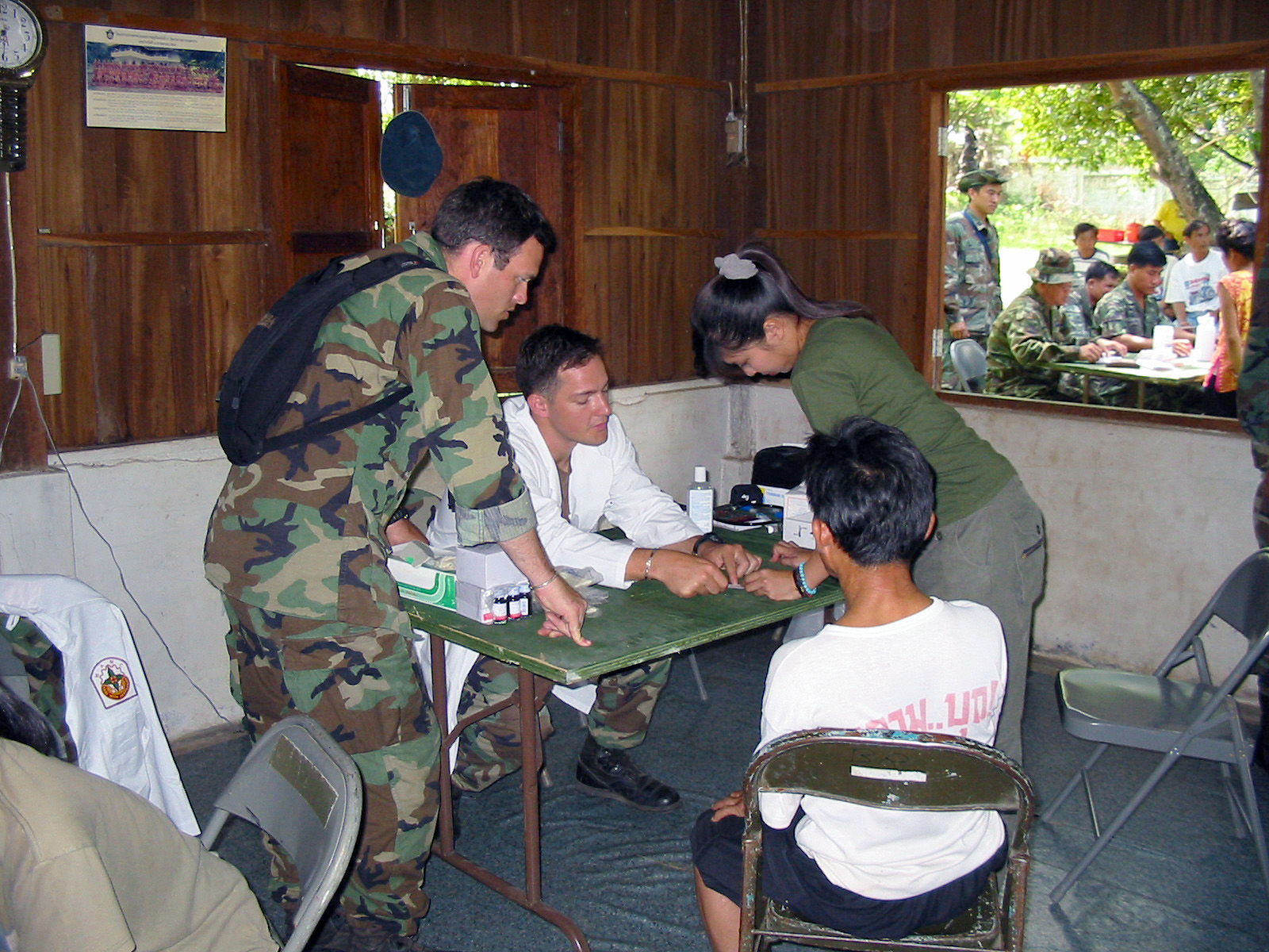 US Army (USA) Medical Doctors assigned to 2nd Battalion, 1ST Special Forces Group (SFG) Airborne, prepare to examine a local Thai man during the Medical Community Assistance Program (MEDCAP) at Ban Dong, Thailand, during Exercise COBRA GOLD 2003