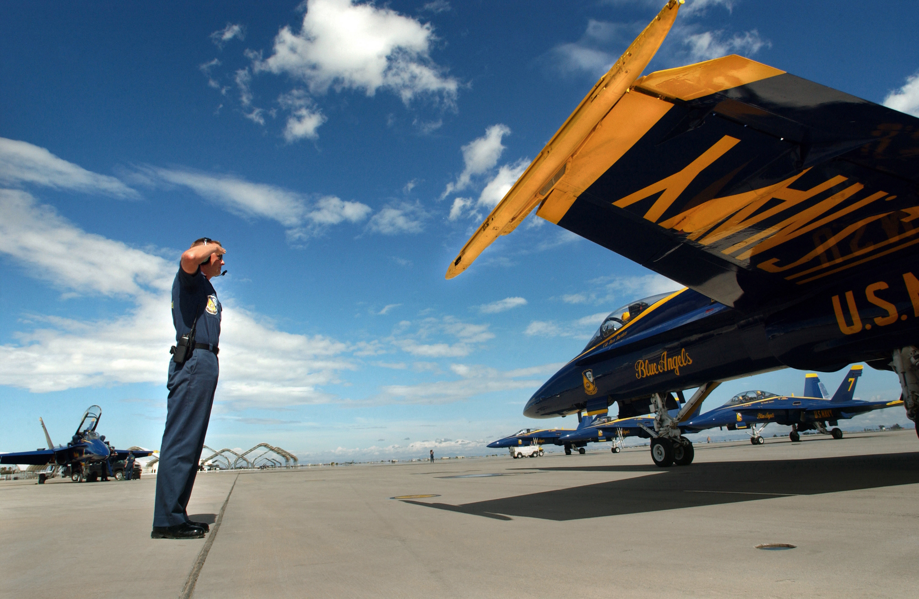 US Navy (USN) Aviation Structural Mechanic First Class (AM1) Ed Pennycook, renders a salute to the flight leader of the USN Blue Angels F/A-18C Hornet aerial demonstration team aircraft as the team taxis onto the runway for a training flight before the Air Show being held at Naval Air Facility (NAF), El Centro, California (CA)