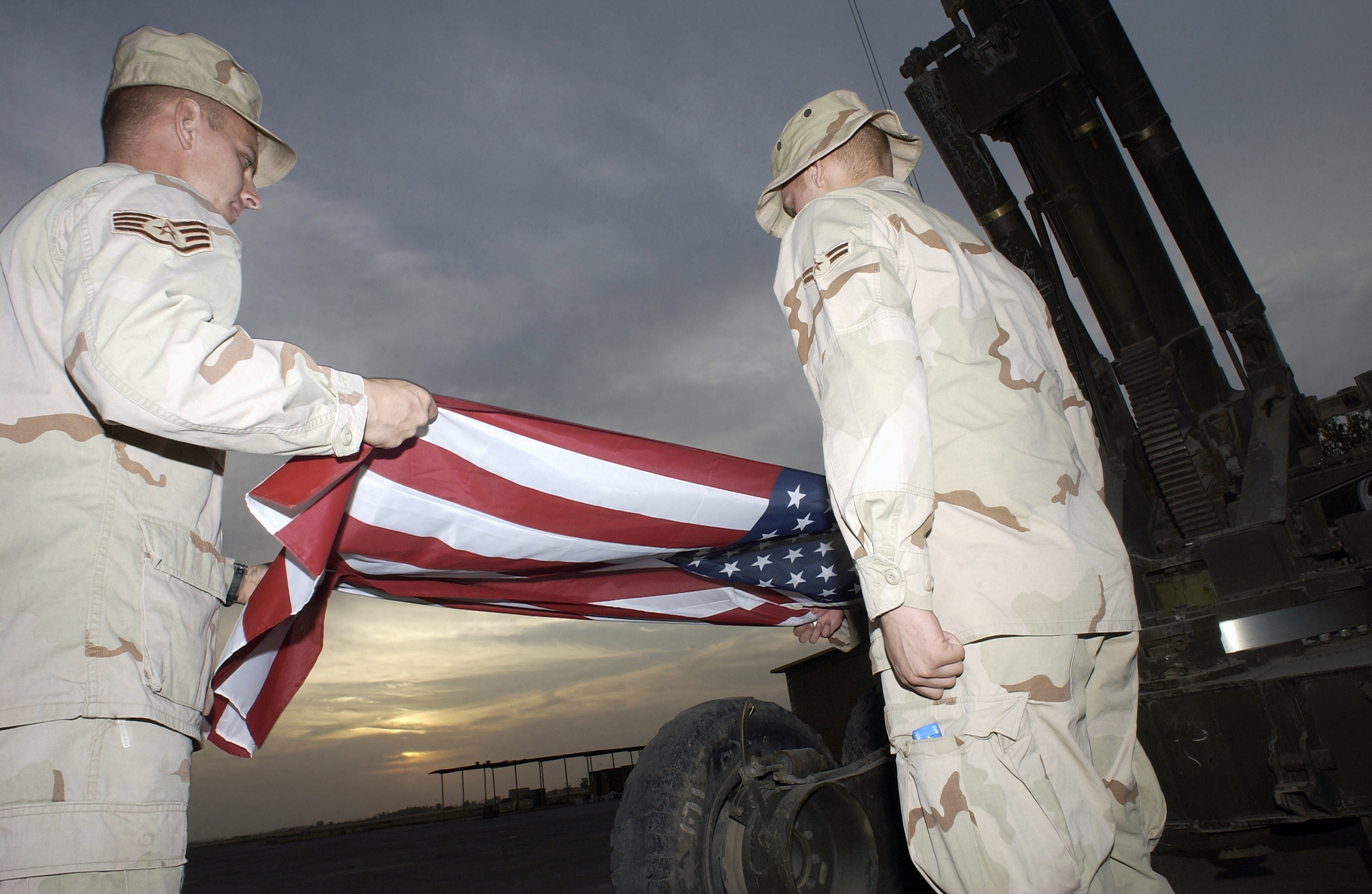 Left to right, US Air Force (USAF) STAFF Sergeant (SSGT) Charles Clawson, AIRMAN First Class (A1C) Jeffrey Wyatt, and A1C Danie Ormsby from the 506th Expeditionary Civil Engineering Squadron (ECES), Fire Department, recover the flag as sunset near at Kirkuk Air Base (AB), Iraq (IRQ), during Operation IRAQI FREEDOM