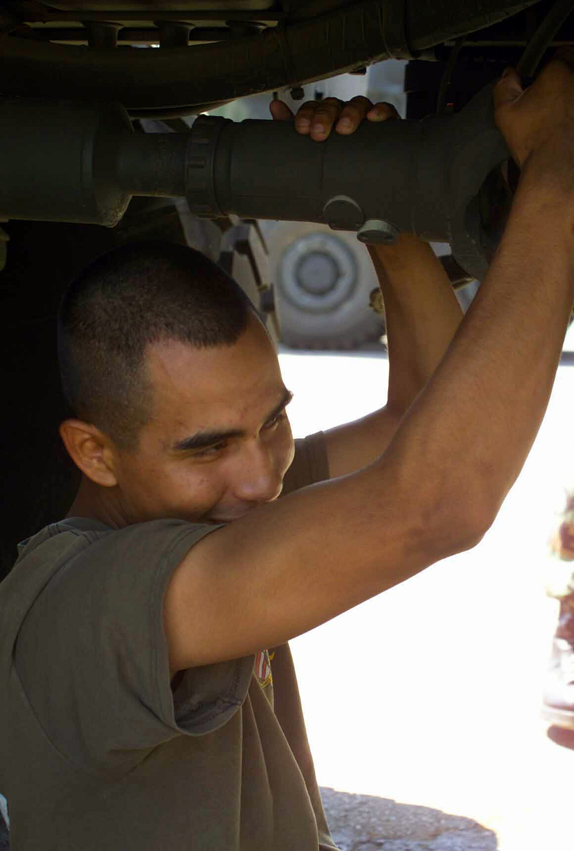 US Marine Corps (USMC) Corporal (CPL) Alejandro Lopez, Motor Transportation Operator, Headquarters Battalion (HQ BN), Truck Company, 1ST Marine Division (MAR DIV), Marine Corps Base (MCB) Camp Pendleton, California (CA), checks the U-joint of a Medium Tactical Vehicle Replacement (MTVR) 7-ton transportation truck in the Companys parking lot. The main goal of Truck Company is to ensure all military vehicles coming their way are in proper working order