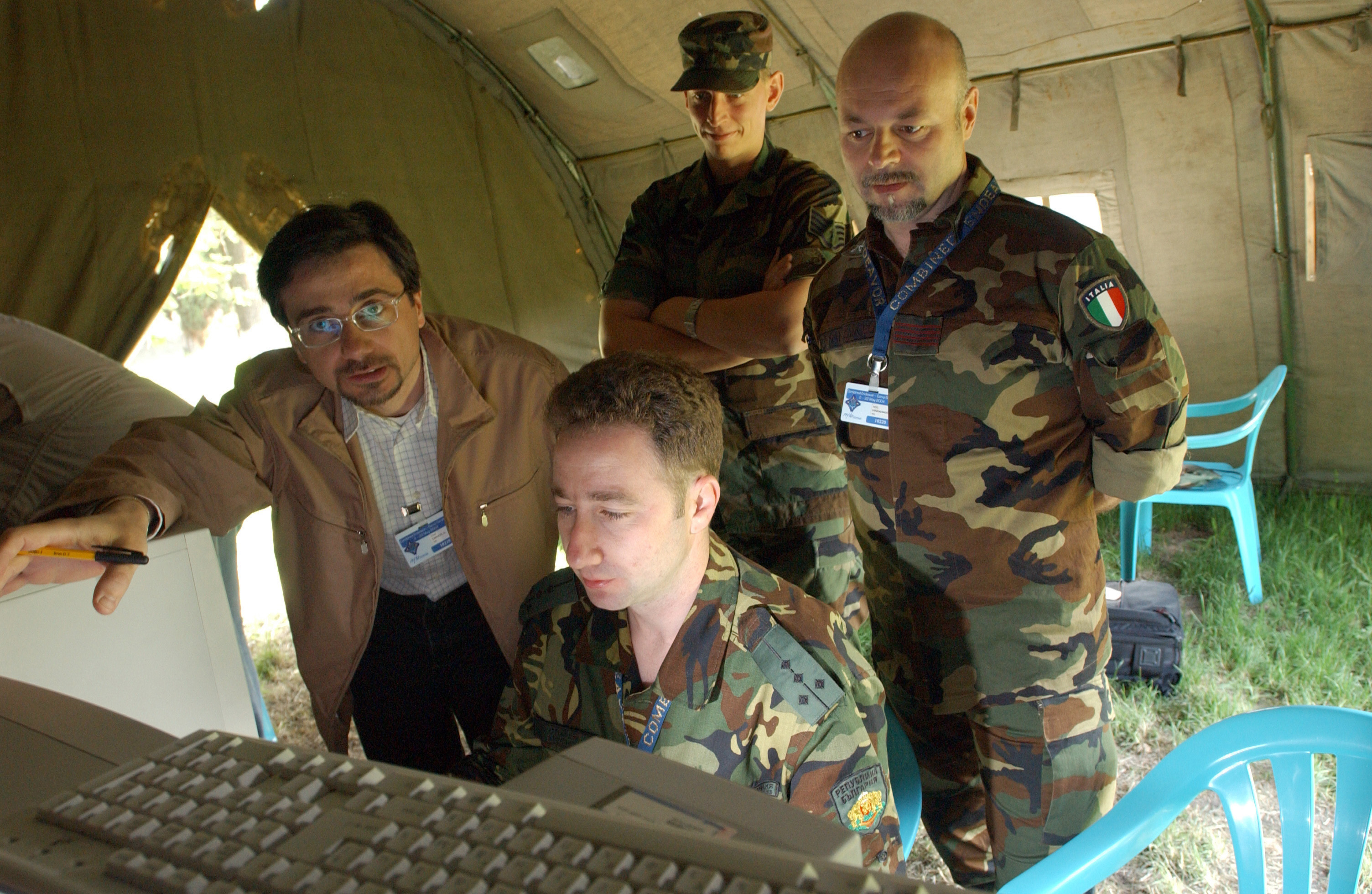During Combined Endeavor 2004, (left to right) Italian Contractor Guseppi Carucci, US Air Force (USAF) STAFF Sergeant (SSGT) Jason Bryant, Italian Warrant Officer 3 (WO3) Sandro Venazangeli and Bulgarian Captain (CPT) Stanislav Stoychev work on encrypted certificates and signature blocks for secure e-mail at Combined Endeavor, Camp Sarafovo, Bulgaria (BGR)