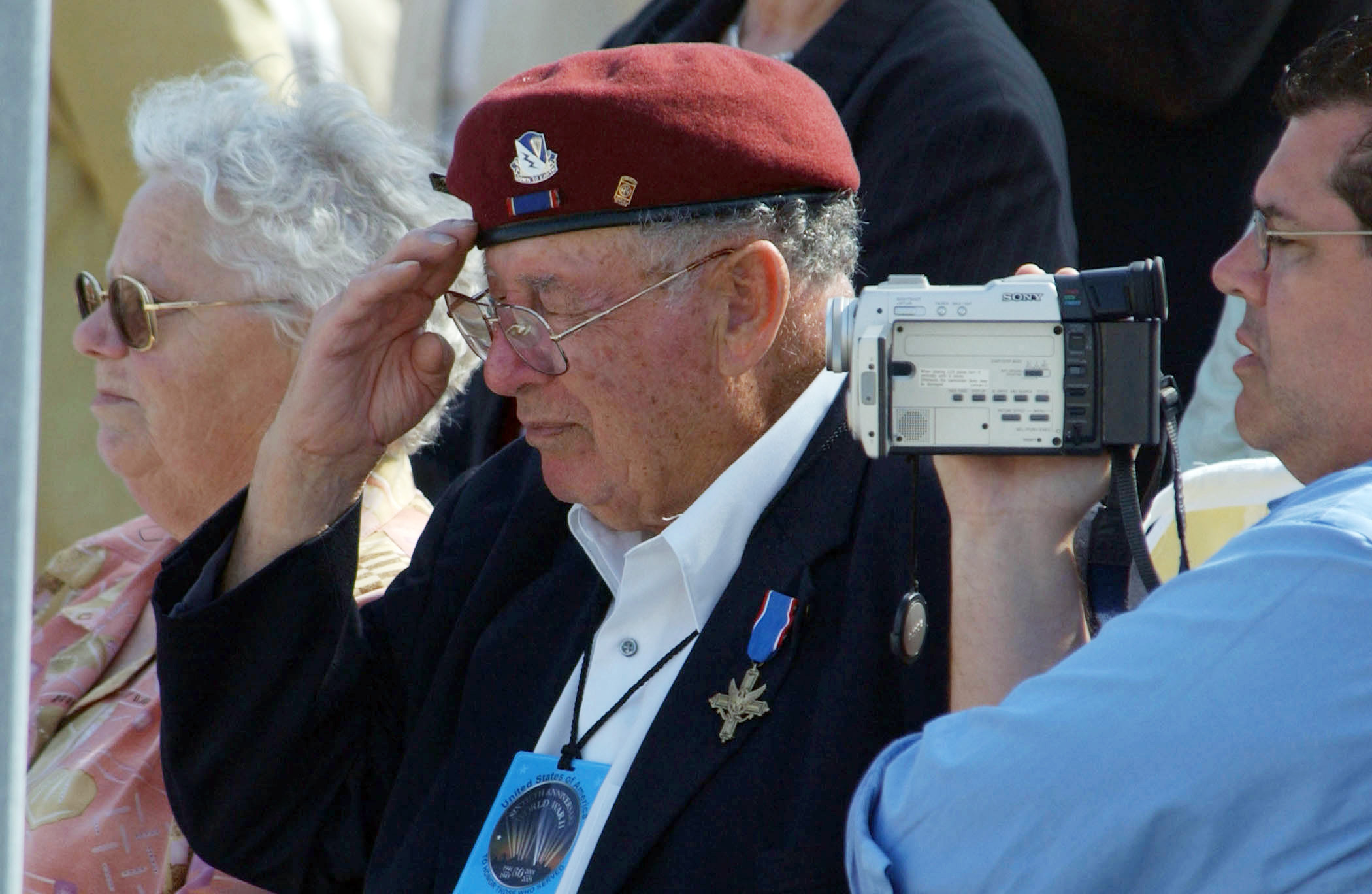 A US Army (USA) 82nd Airborne Division World War II veteran, displaying his earned Distinguished Service Cross (DSC), renders a salute during the playing of the National Anthems at Utah Beach during a ceremony commemorating the 60th Anniversary of the D-Day landings