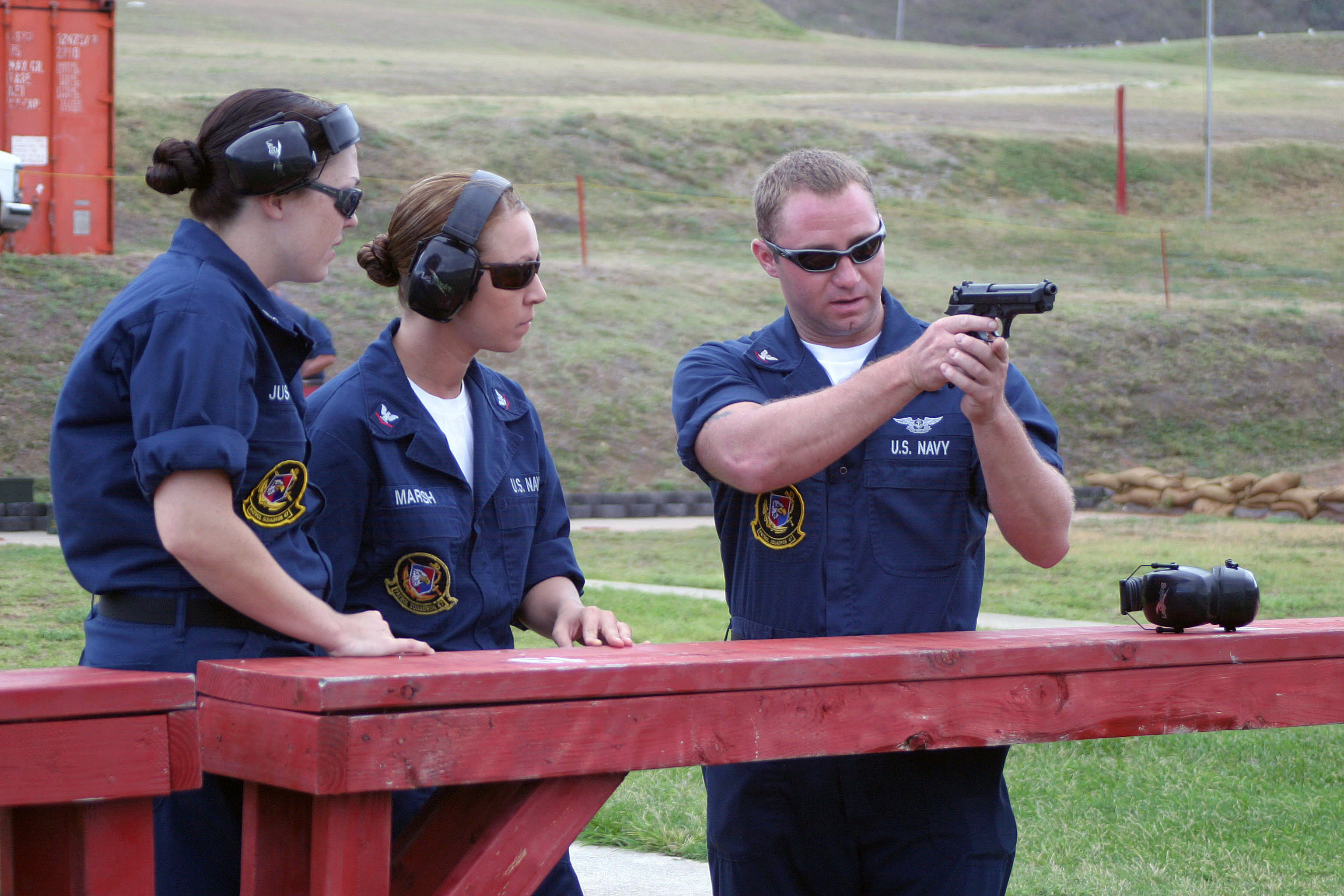 US Navy (USN) Aviation Ordnanceman Third Class (Air Warfare) (AO3(AW)) Justin Matt (right) instructs USN Aviation Electrician Third Class (AE3) Michele Justice (left) and USN AO3 Marisa Marsh on the proper firing technique of a 9mm M9 Pistol. Small arms qualifications are held for all personnel of Patrol Squadron 47 (VP-47), Marine Corps Base (MCB) Hawaii, Kaneohe Bay, Hawaii (HI), in preparation for deployment