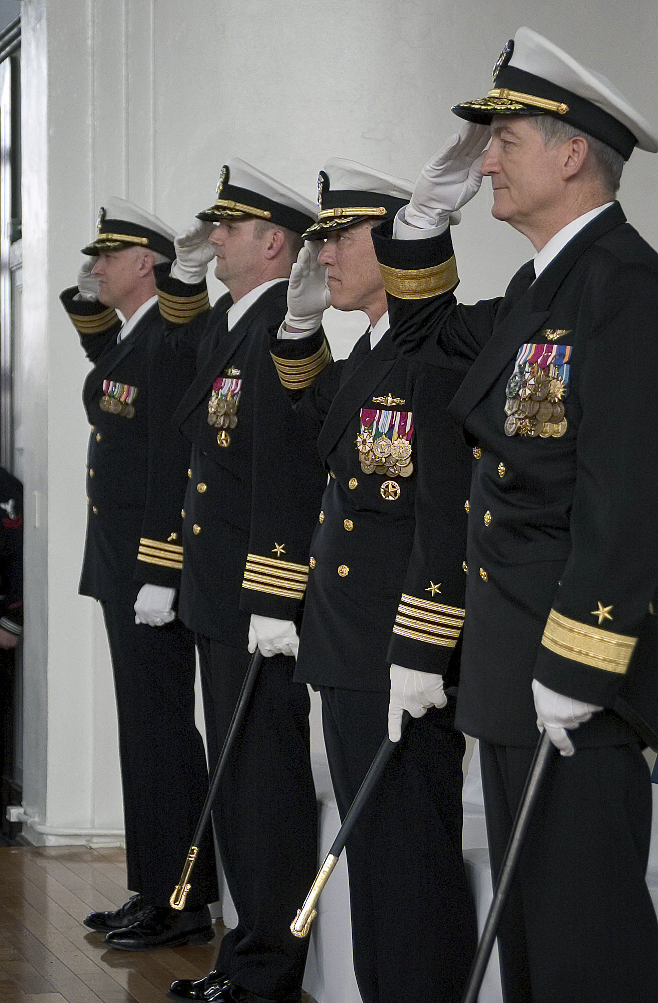 US Navy (USN) Commander (CDR) Wayne R. Freiberg (left), Chaplain; USN Captain (CAPT) Gregory J. Cornish, Commanding Officer (CO), prospective Commander Fleet Activities Yokosuka (CFAY); USN CAPT King H. Dietrich, CFAY CO; and USN Rear Admiral (RDML) (lower half) James D. Kelly (right), Commander Carrier Strike Group 5 (CSG-5) salute the colors as the National Anthems of Japan and the United States are sung during the CFAY change of command ceremony. USN CAPT Cornish relieved USN CAPT Dietrich as CFAY Commanding Officer