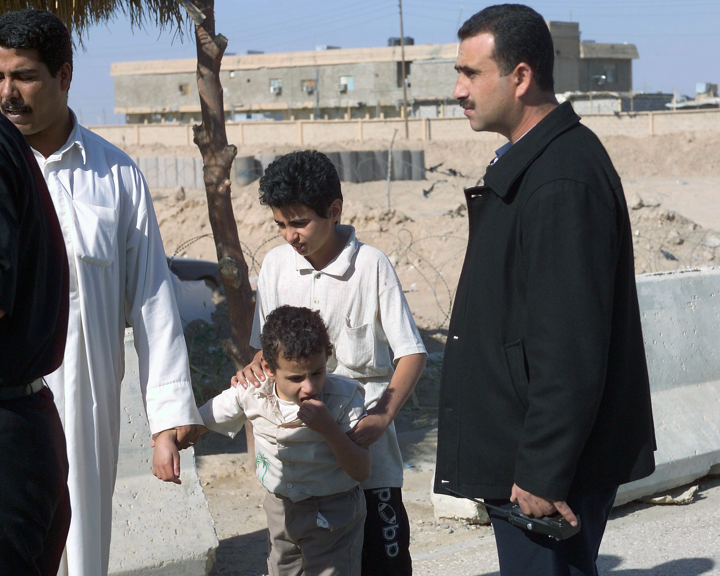 Two Jordanian Medical Doctors (left and right) talk with an Iraqi father (second from left) about his two sons at an Iraqi Army controlled humanitarian assistance site on Nov. 20, 2004, in the city of Fallujah, Al Anbar Province, Iraq. The younger son (center) is sick and will be taken to a Jordanian operated hospital by an armed military convoy. Iraqi civilians are able to come to this site to receive humanitarian assistance at the conclusion of the week-long battle by Multinational Forces against insurgents in the city of Fallujah, during Operation Iraqi Freedom. (U.S. Marine Corps photo by CPL. Theresa M. Medina) (Released)