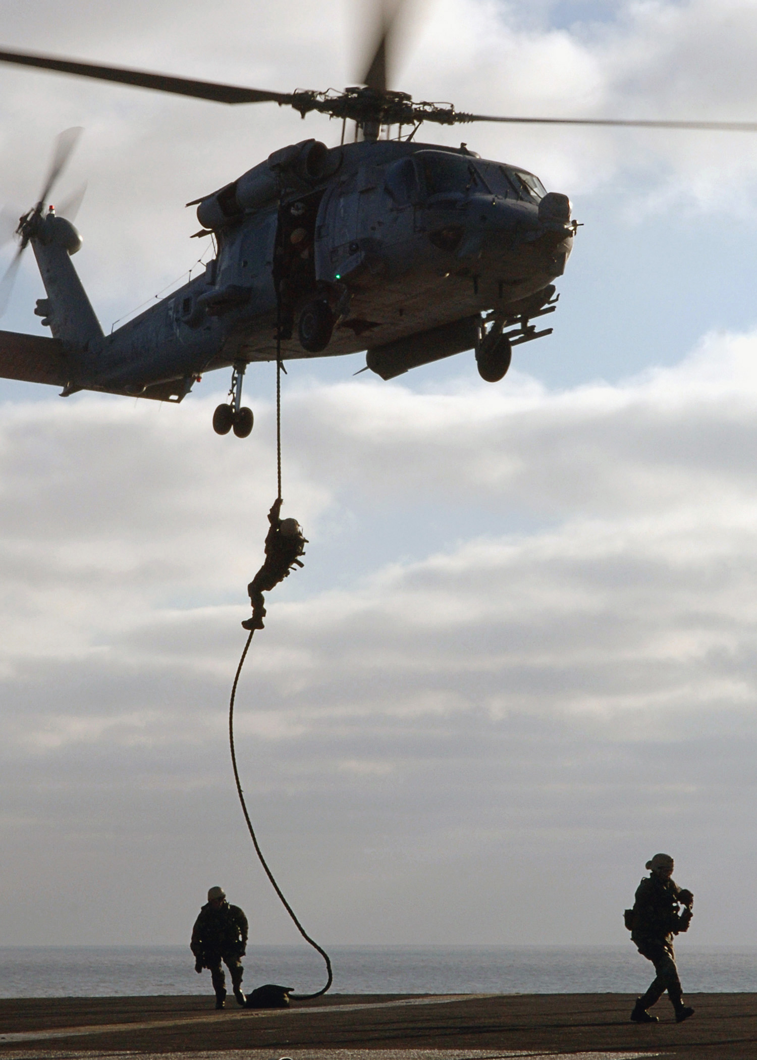 US Navy (USN) Sailors assigned to Explosive Ordnance Disposal, Mobile Unit 6 (EODMU-6), Detachment 14 (DET-14), fast ropes from a hovering USN SH-60F Sea Hawk helicopter from Helicopter Anti-Submarine Squadron 11 (HS-11), onto the flight deck of the USN Aircraft Carrier, USS ENTERPRISE (CVN 65). The ENTERPRISE and embarked Carrier Air Wing 1 (CVW-1) are currently underway on a scheduled six-month deployment in support of the global war on terrorism